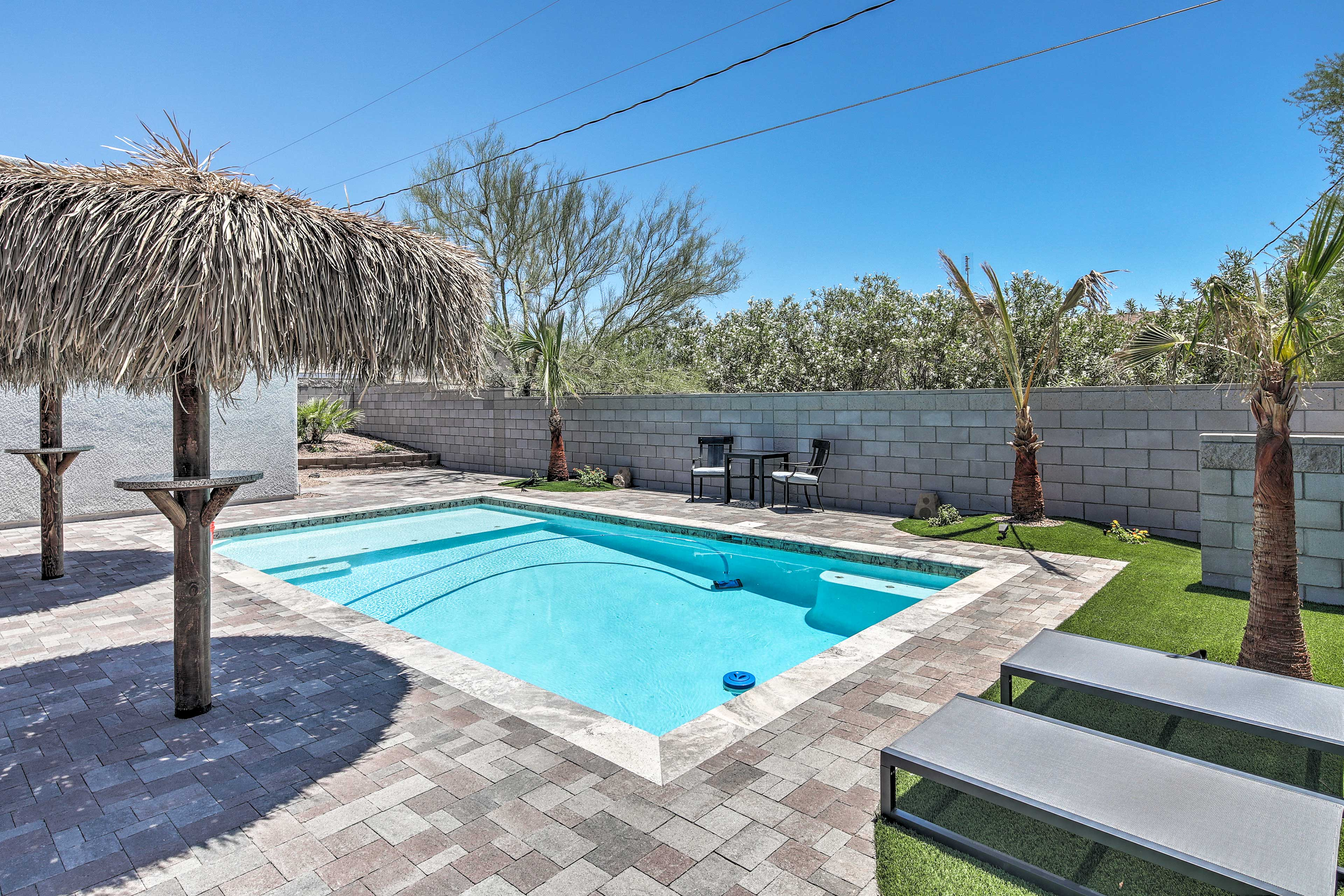 The pool deck is furnished with lounge chairs and a small dining table.
