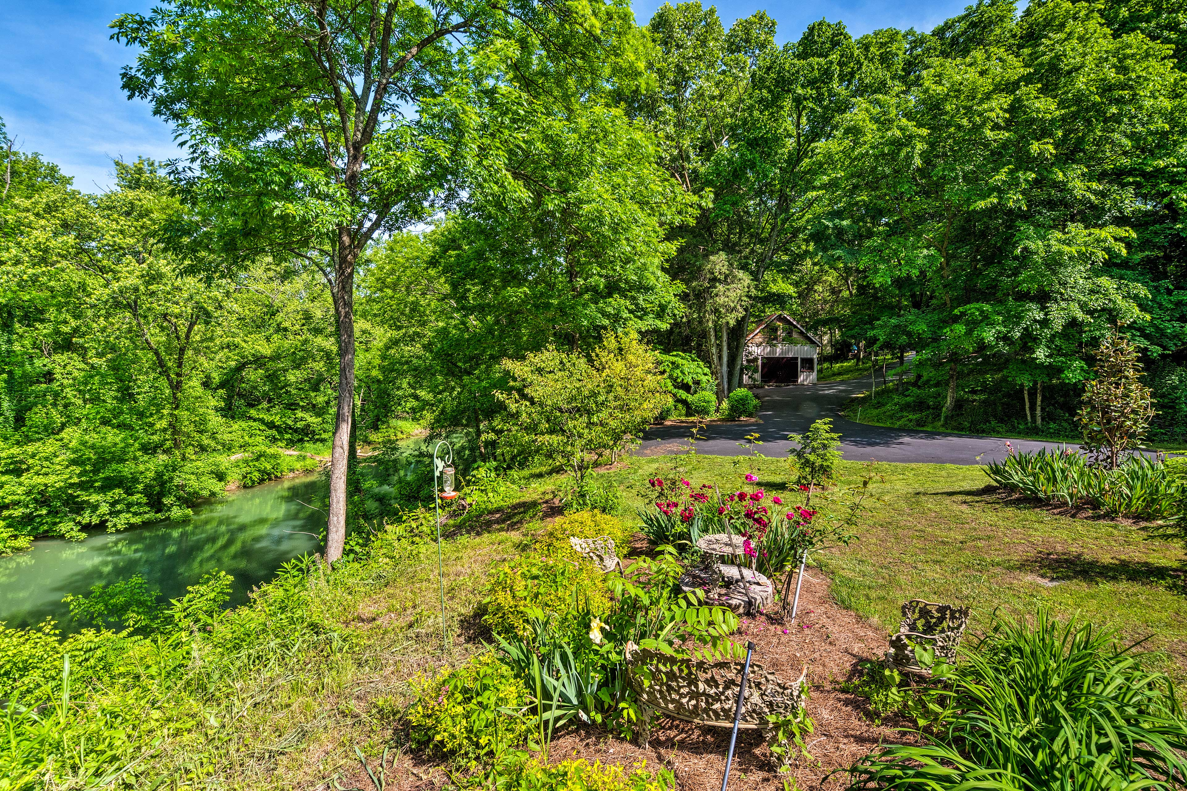 The beautiful outdoor space includes a garden, picnic table, and swinging bench.