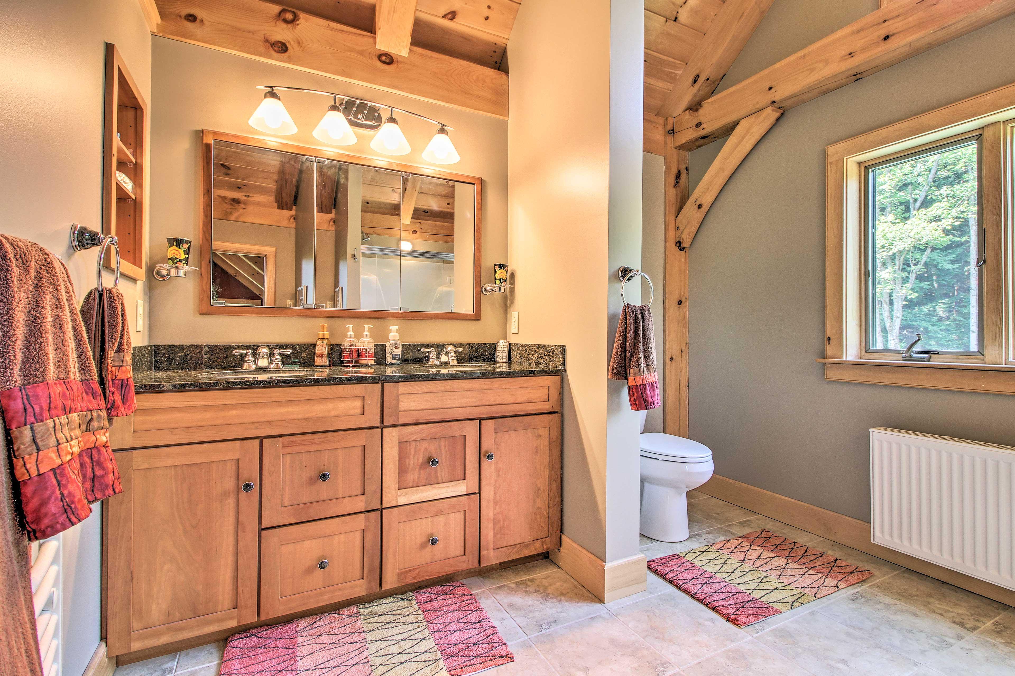 The en-suite bathroom has a dual sink vanity.
