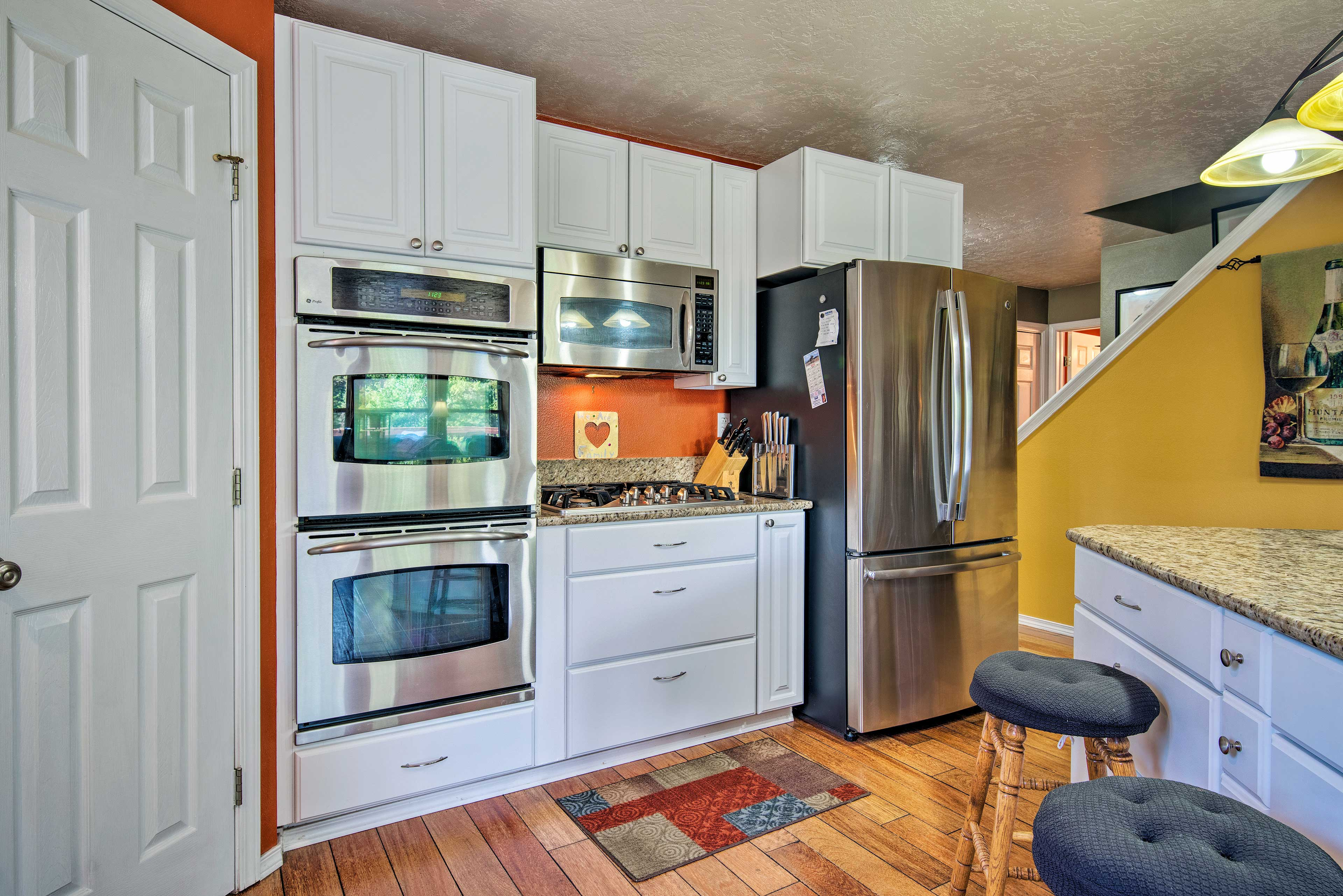 The full kitchen has stainless steel appliances and granite countertops.