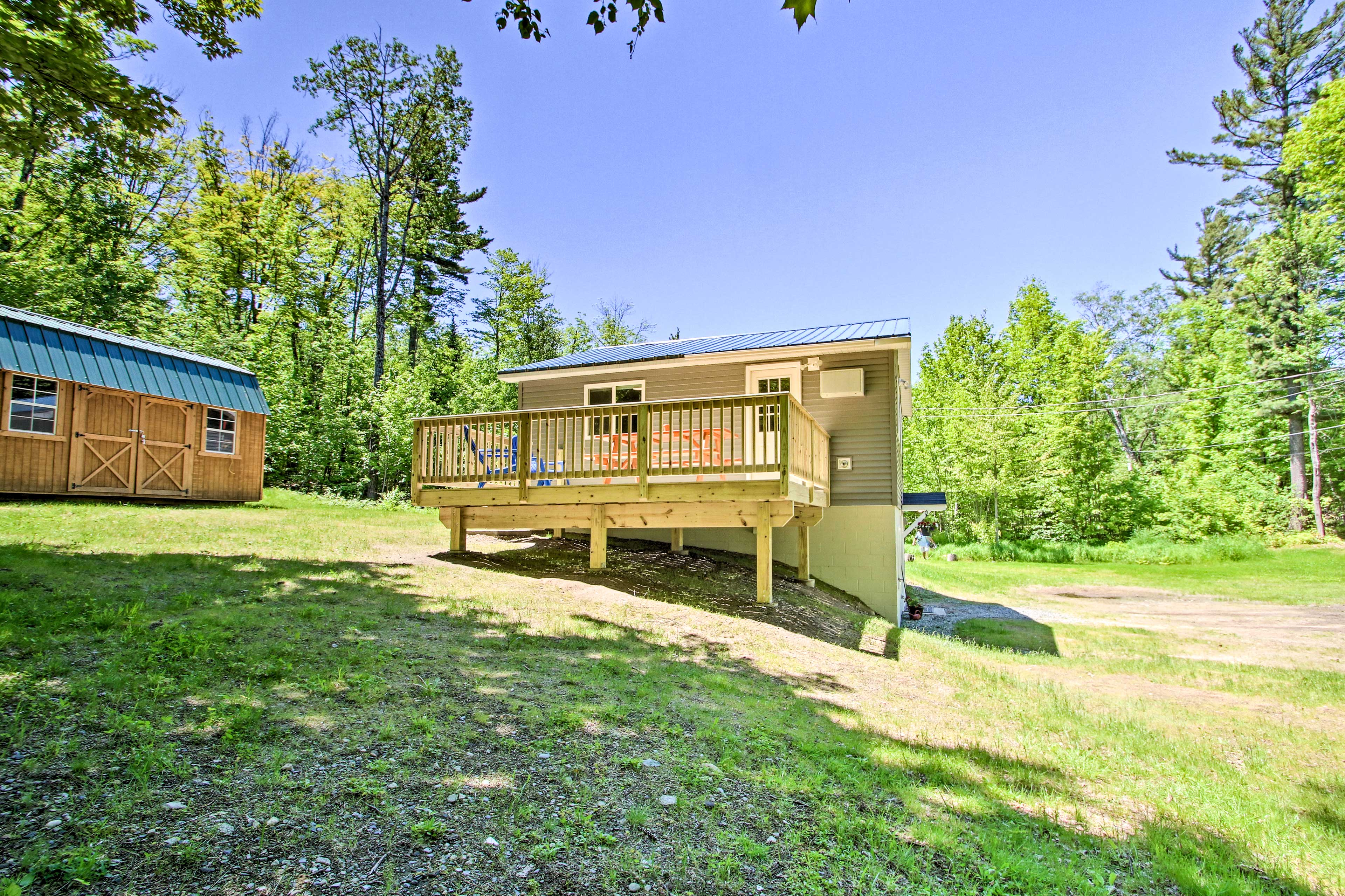 The vacation rental sits on an open clearing surrounded by trees.
