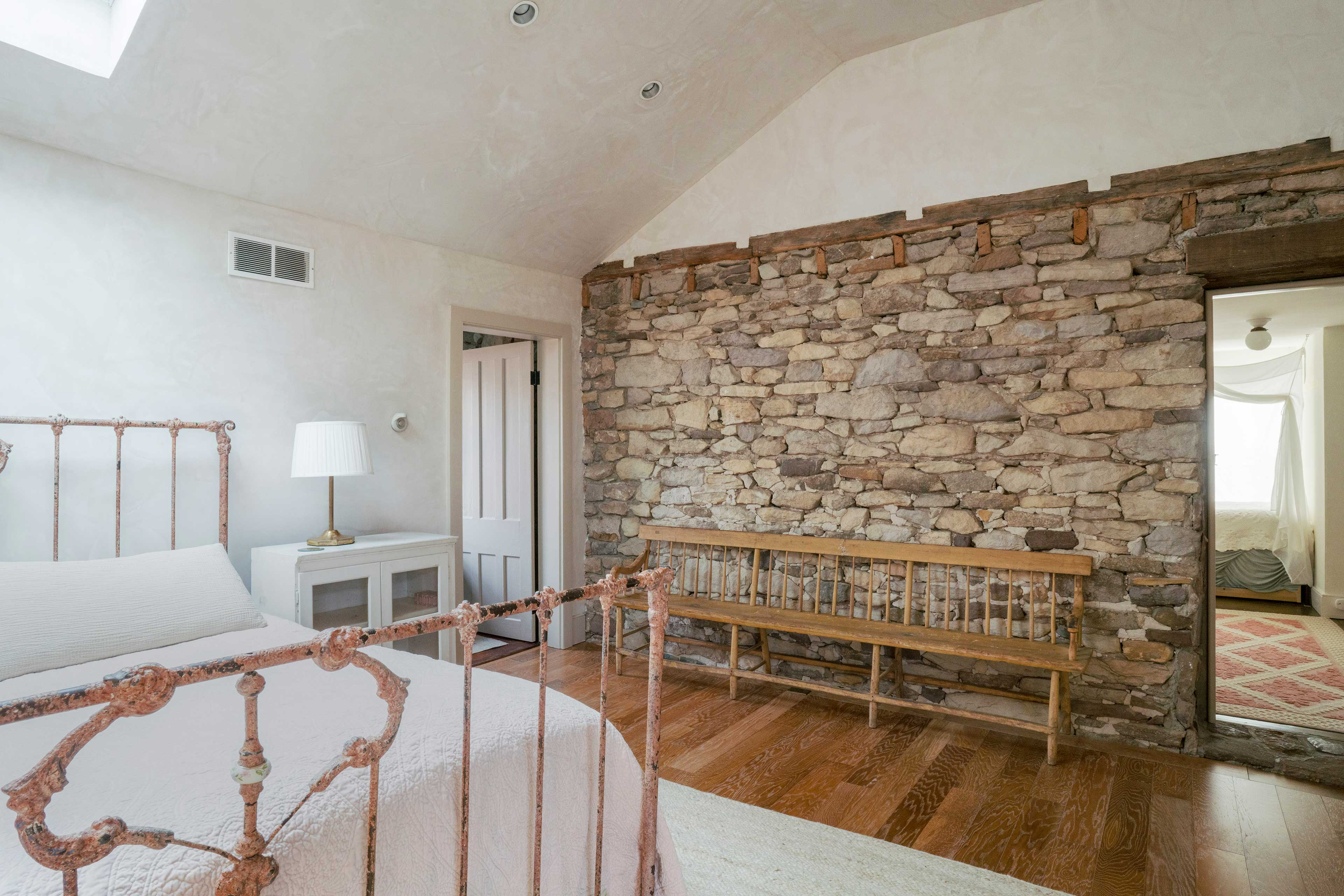 The master bedroom boasts a king-sized bed and original wall section.