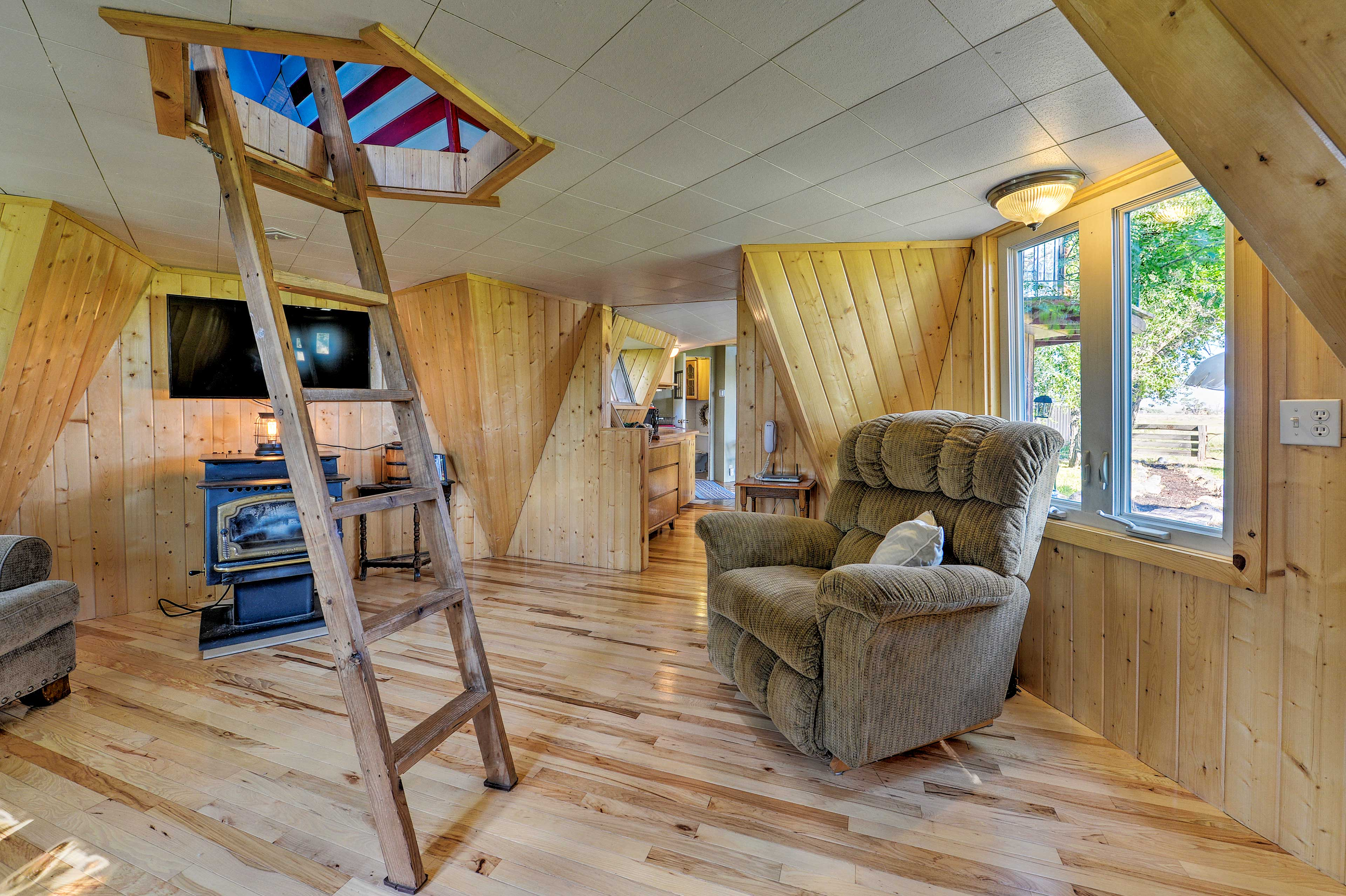 The living room features a ladder to the loft area.