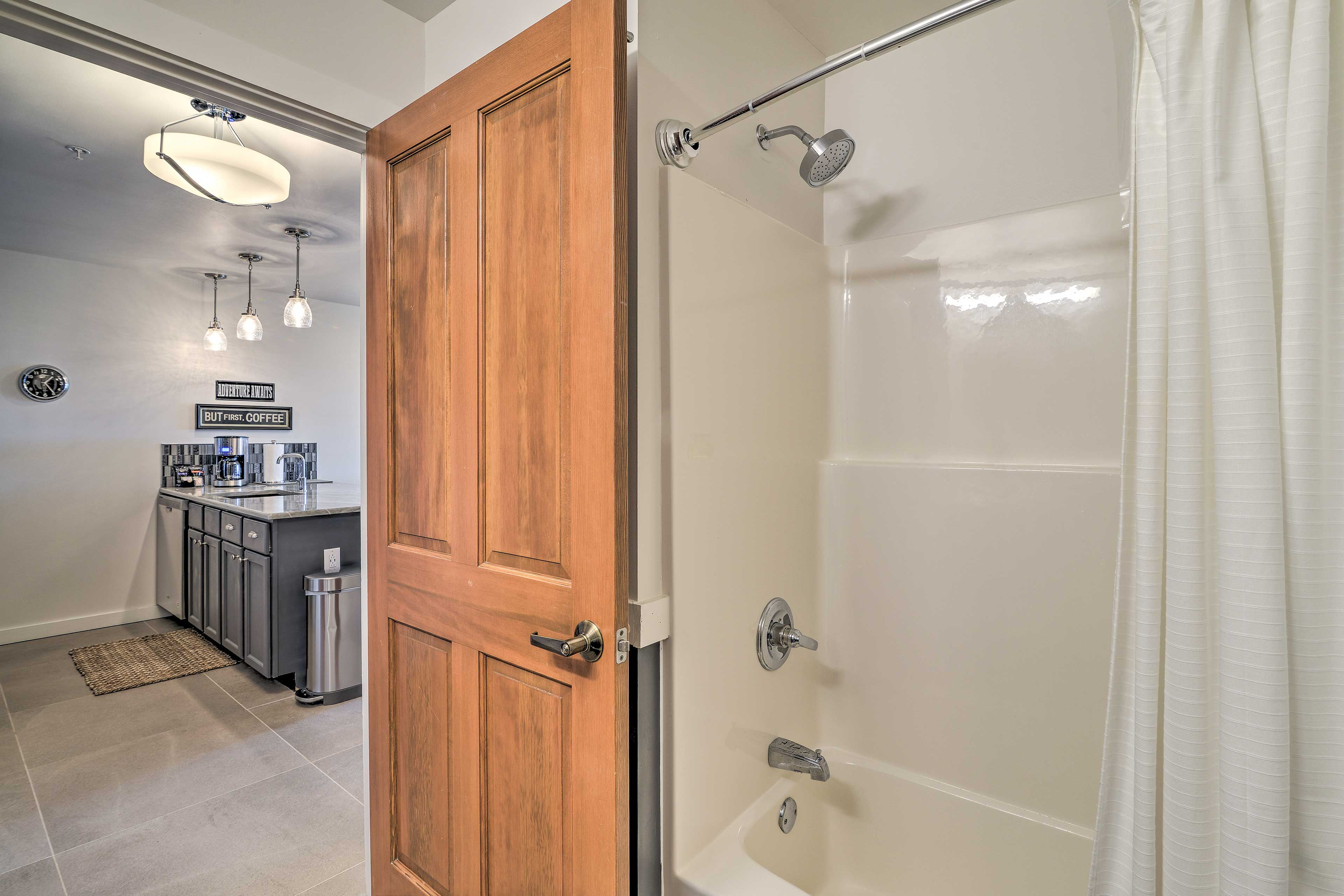 The bathroom features a shower/tub combo along with fresh towels.