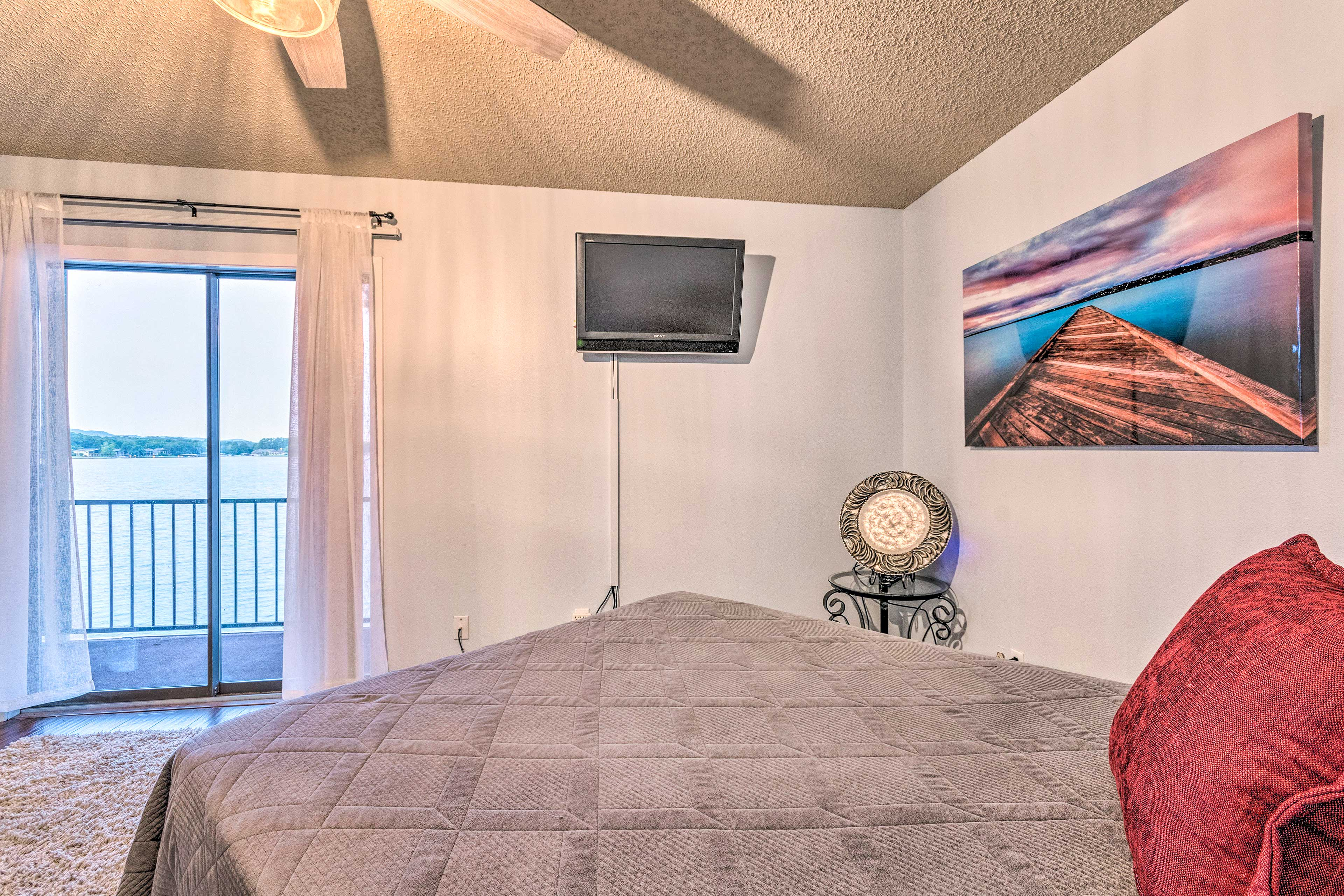 The master bedroom boasts a queen bed and balcony access.