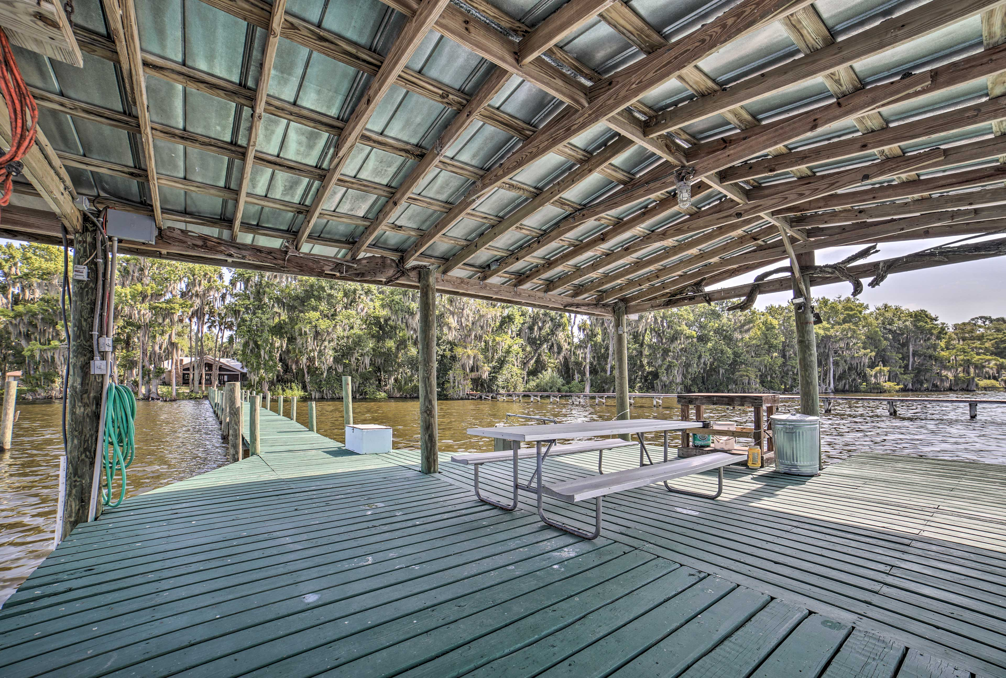The dock boasts a boat slip, picnic table, and covered area.