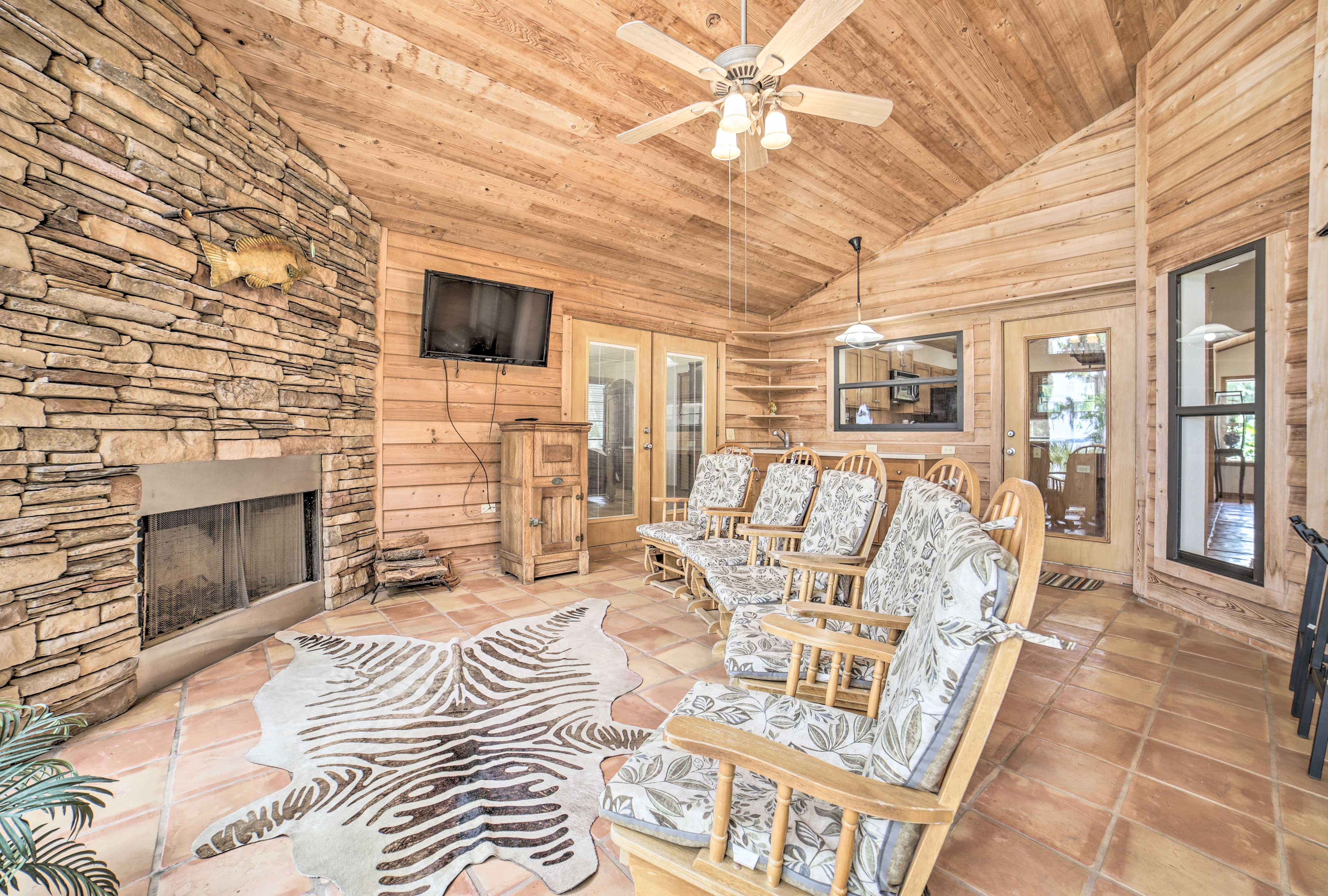This room features a flat-screen TV, fireplace, rocking chairs, a grill & more!