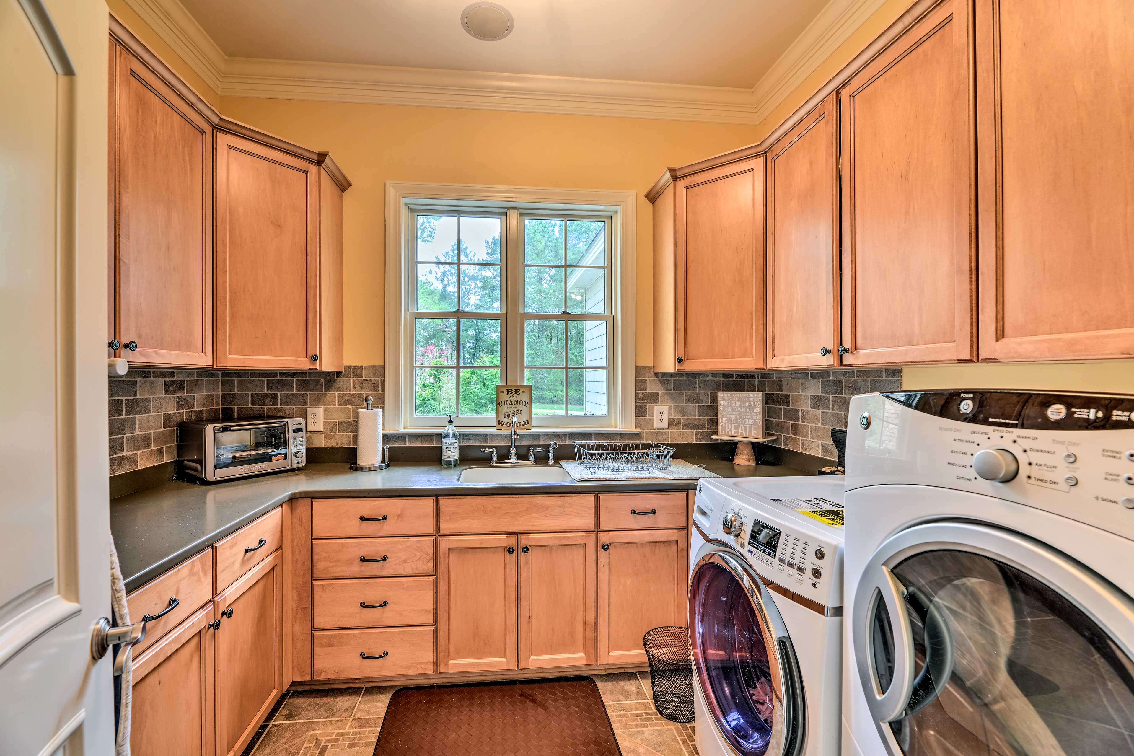 The laundry room has additional storage, a sink, and toaster oven.