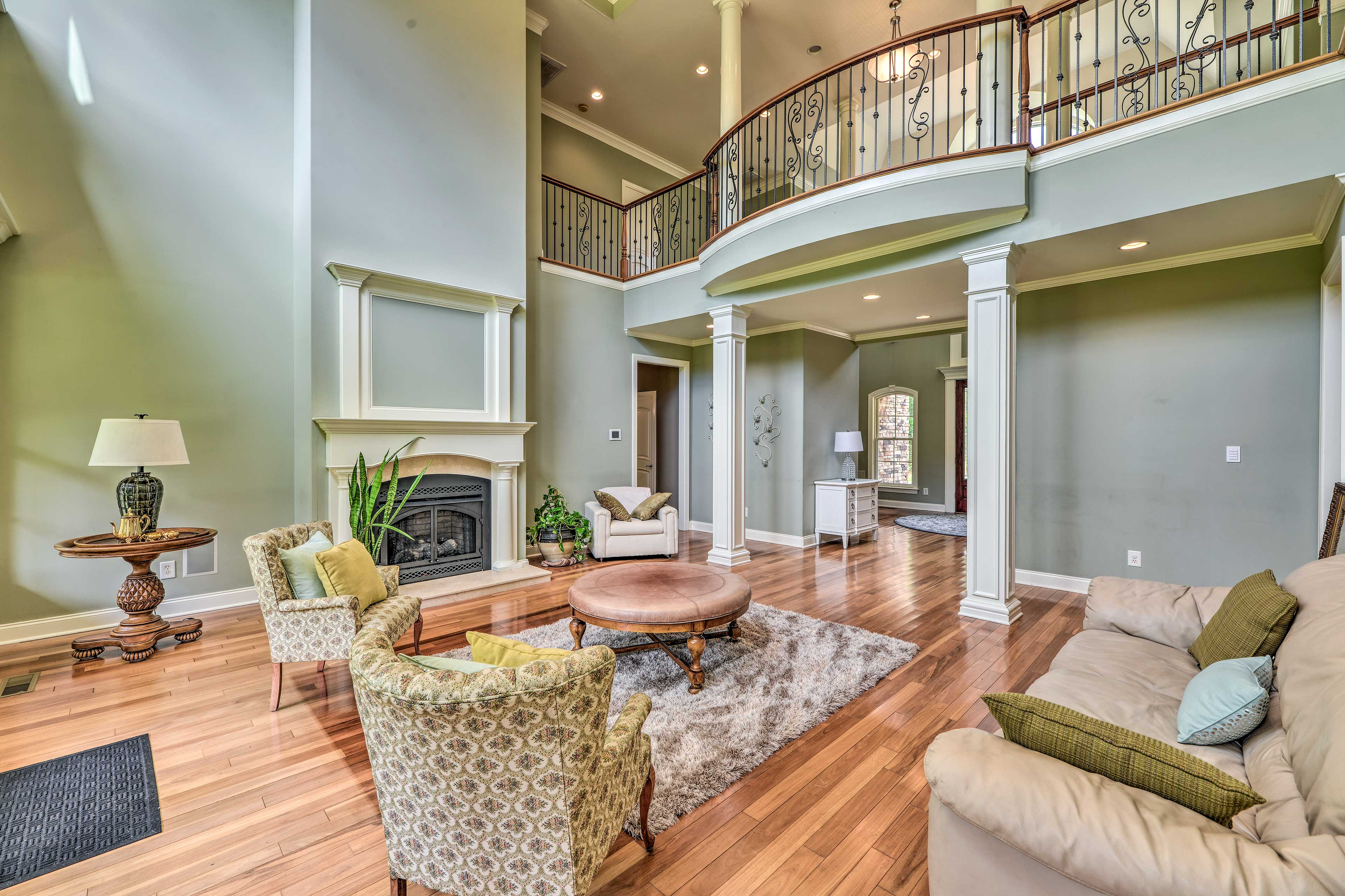 The formal sitting room features  plenty of places to relax and a fireplace.