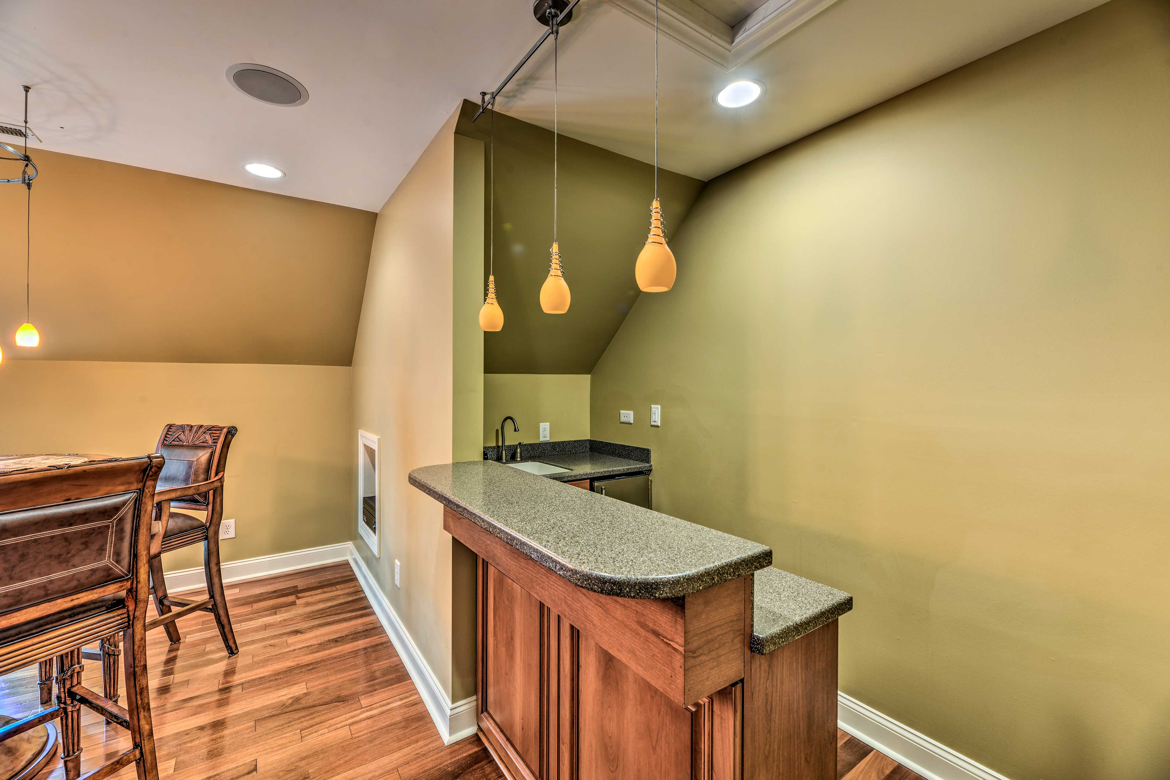 The space includes a wet bar and high-top table.