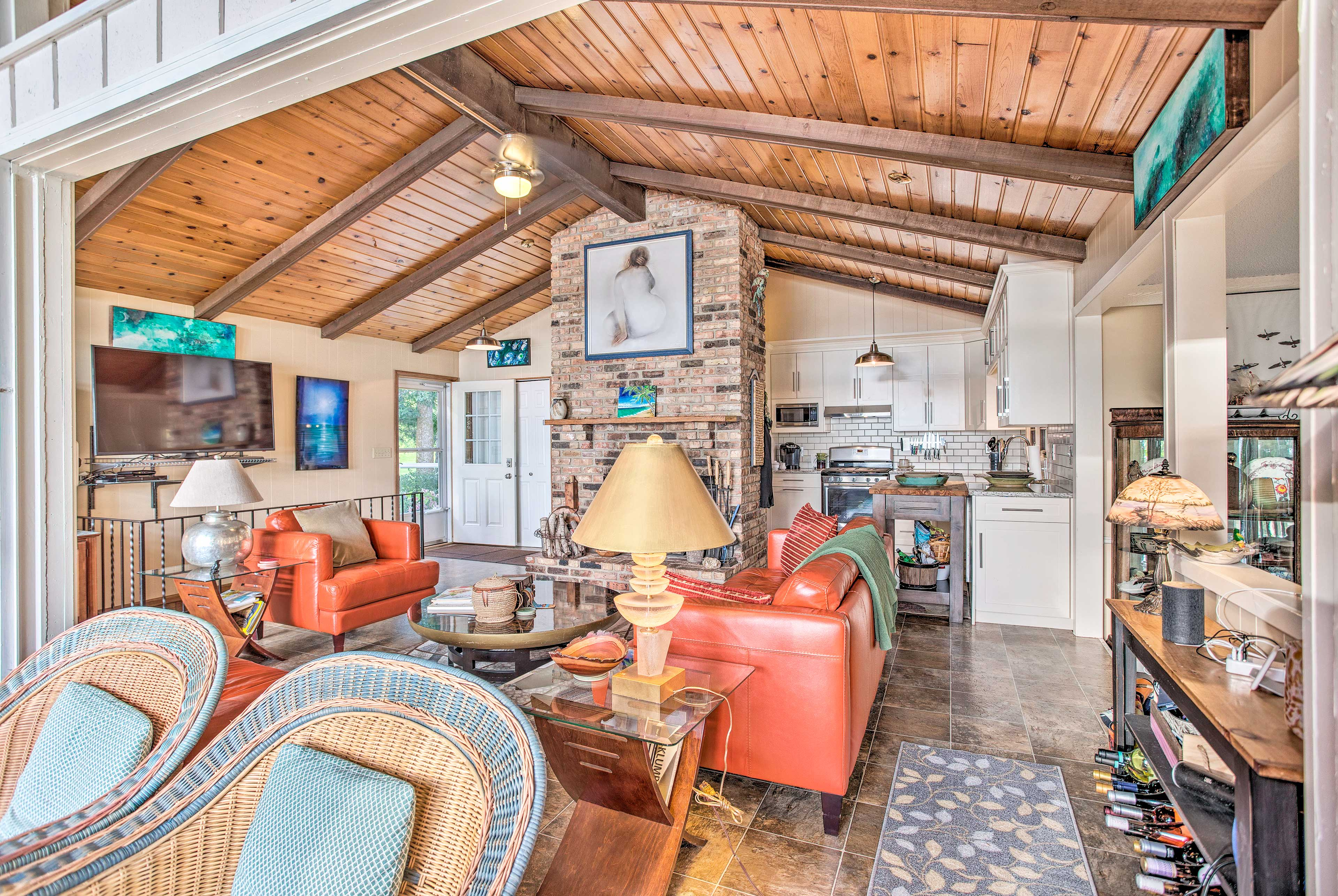 The vaulted ceiling boasts open beams, stretching over the living area.