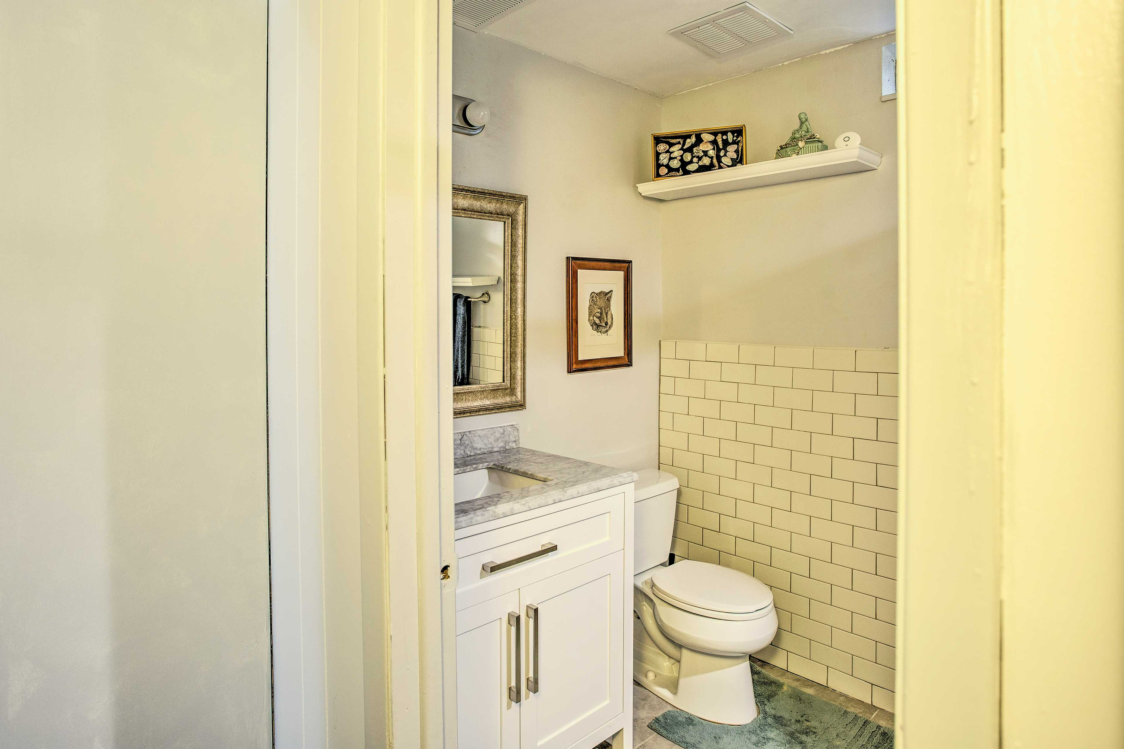 The second full bathroom is outfitted with subway tiles and marble counters.