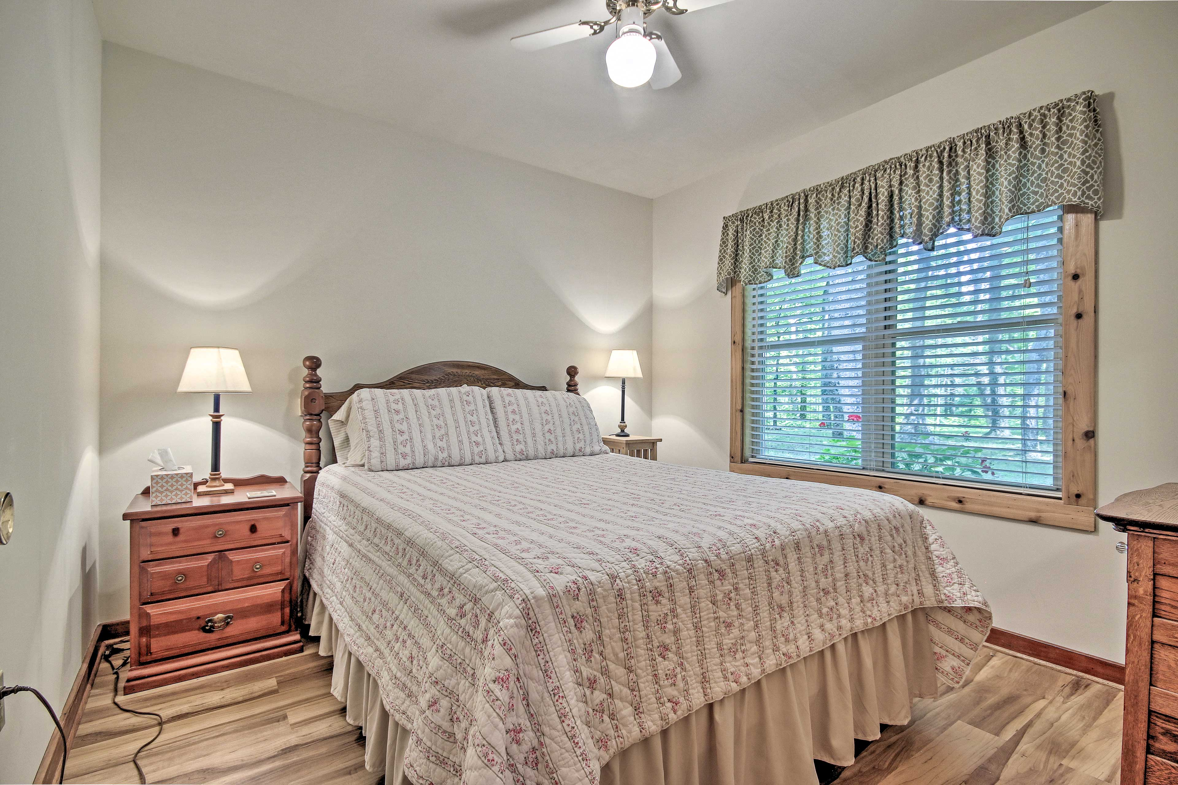 This room features a queen bed and storage space in the nightstand or dresser.