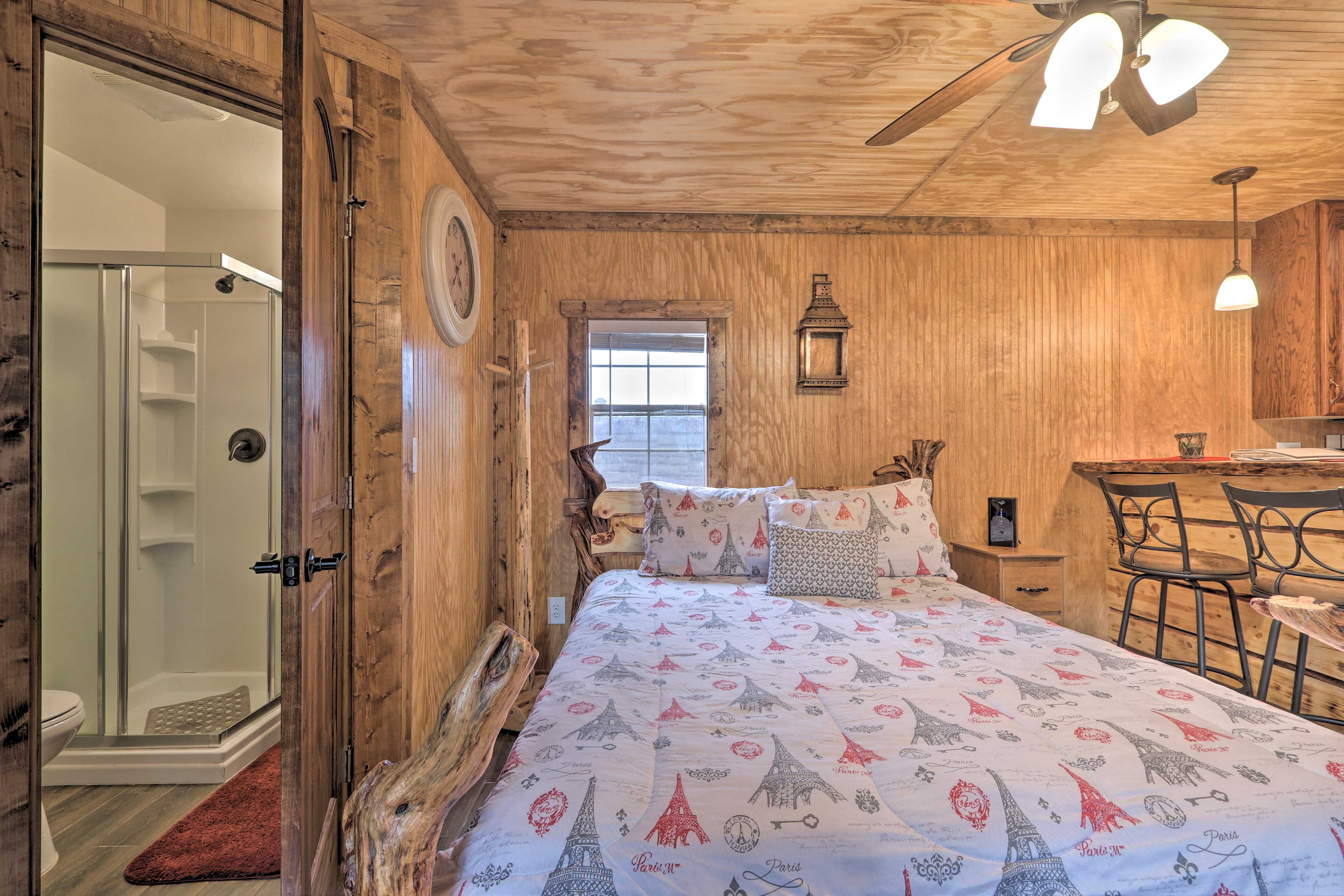 The bathroom is located next to the queen bed.