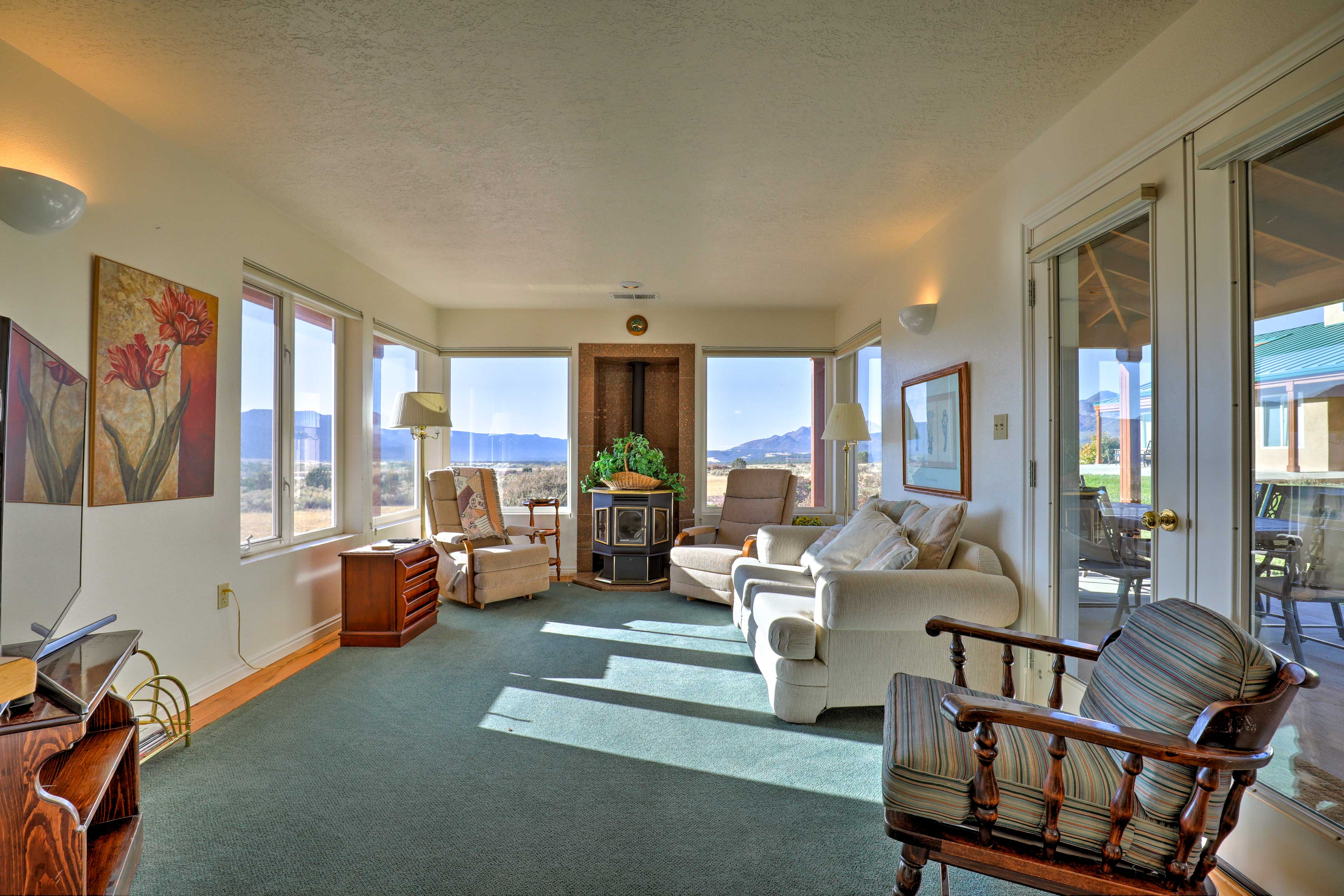The cozy family room doubles as a sunroom with large picture windows.