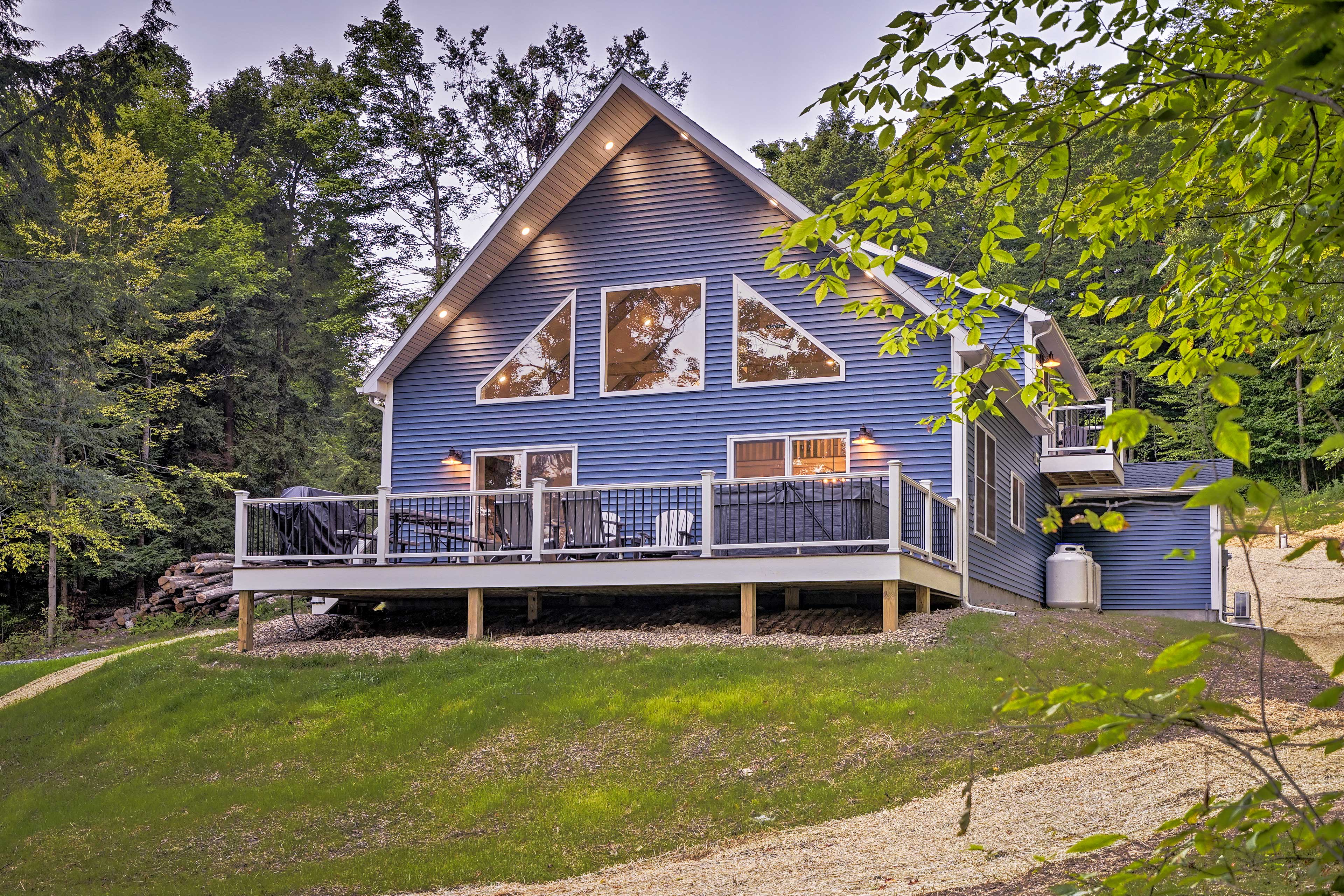 The deck is loaded with amenities including a hot tub, grill, and dining area.