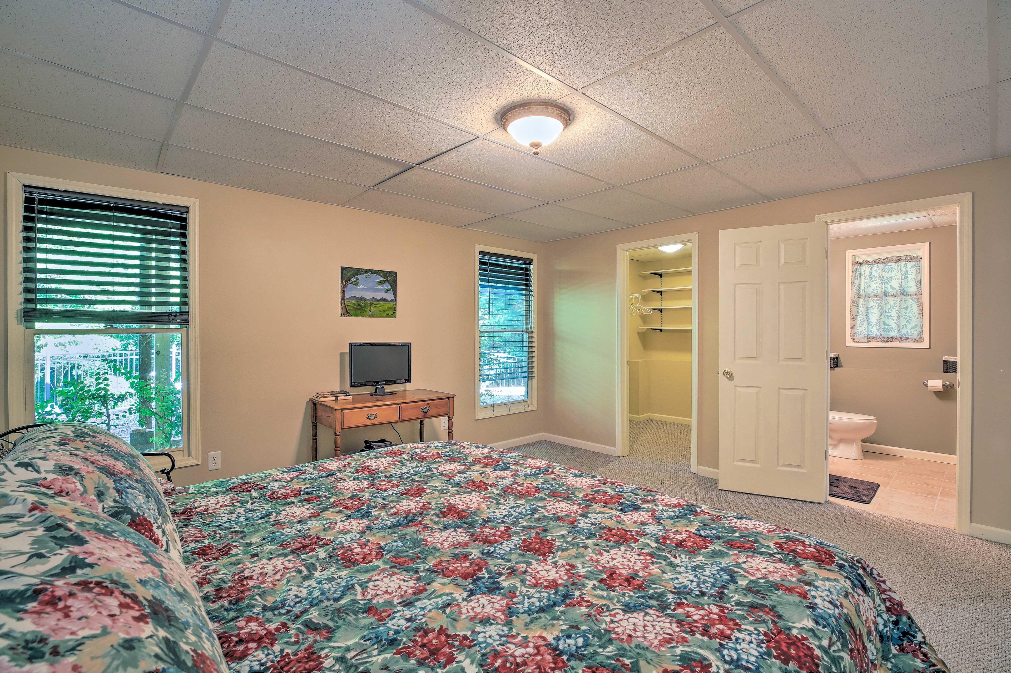 This bedroom hosts a queen bed, computer monitor and en-suite bathroom.