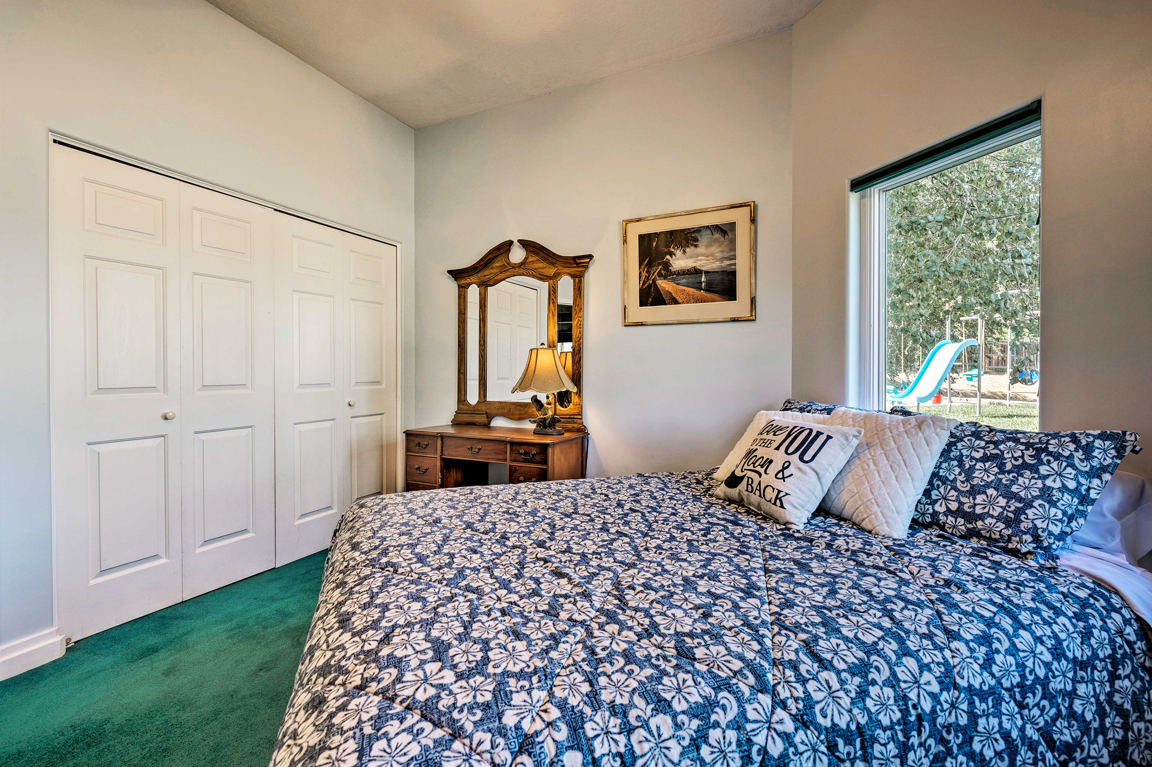 Large windows and a queen-sized bed complete this room.