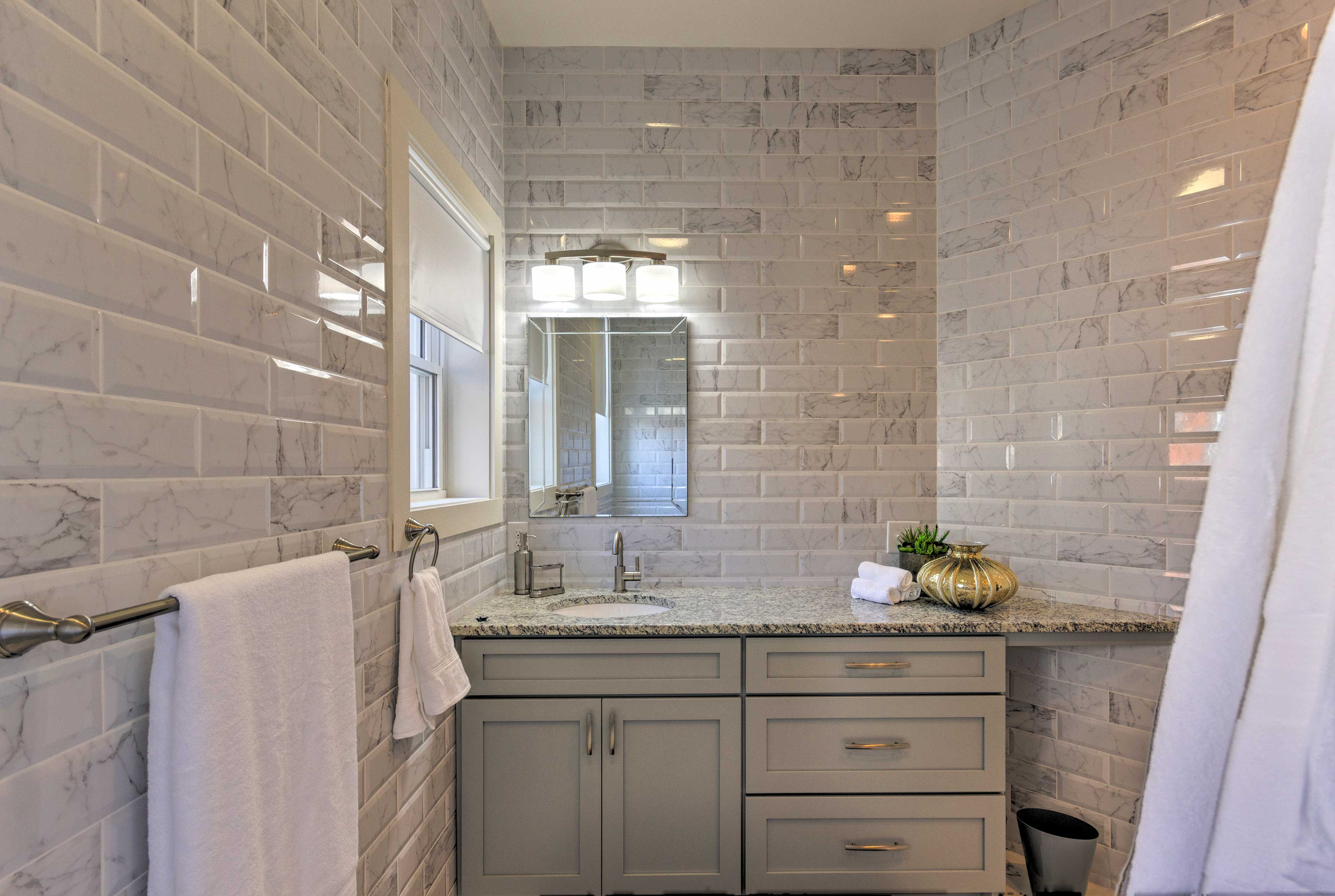 Tiled marble walls frame the bathroom.