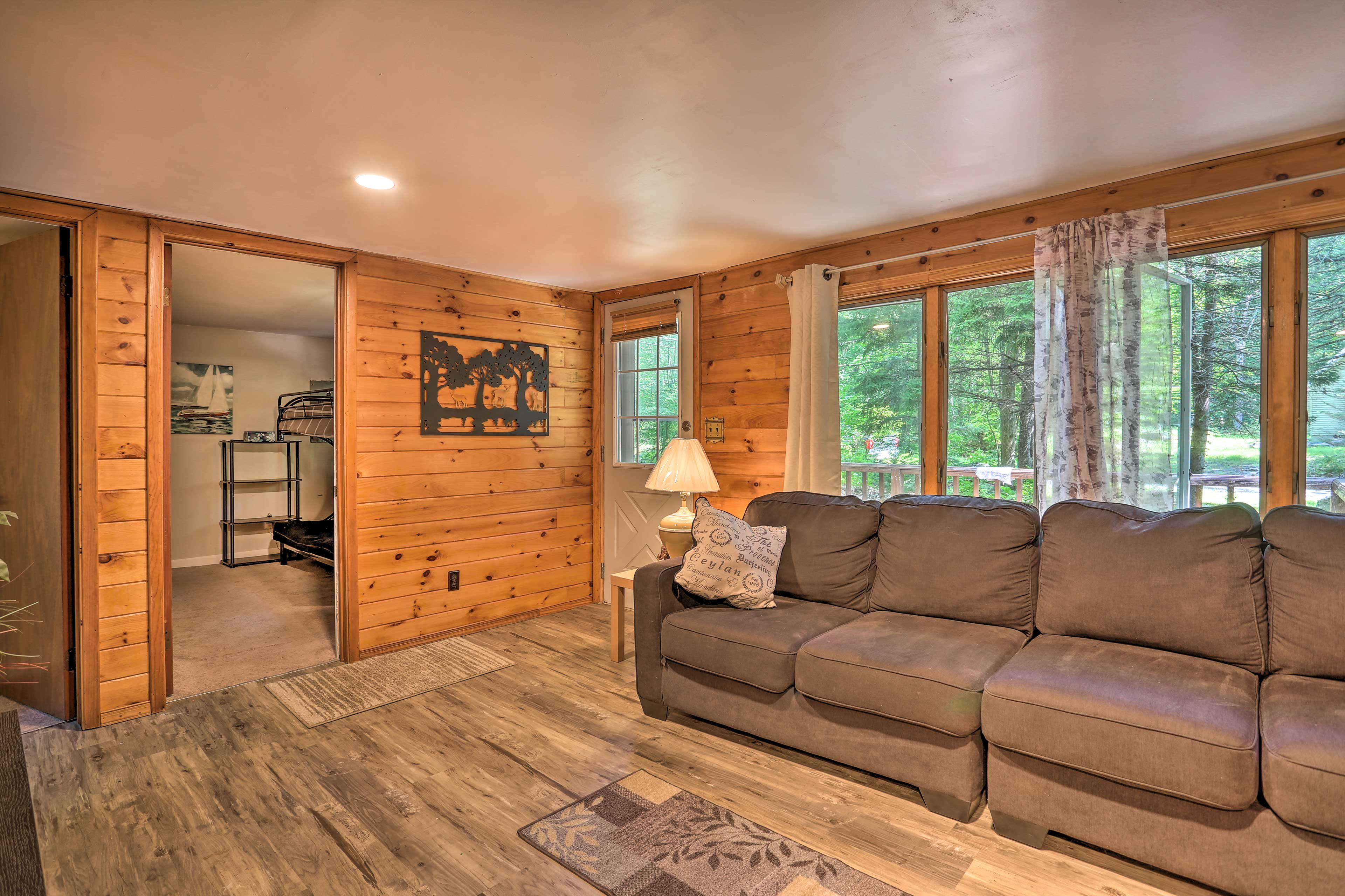 The living room features country-chic decor and pine details.