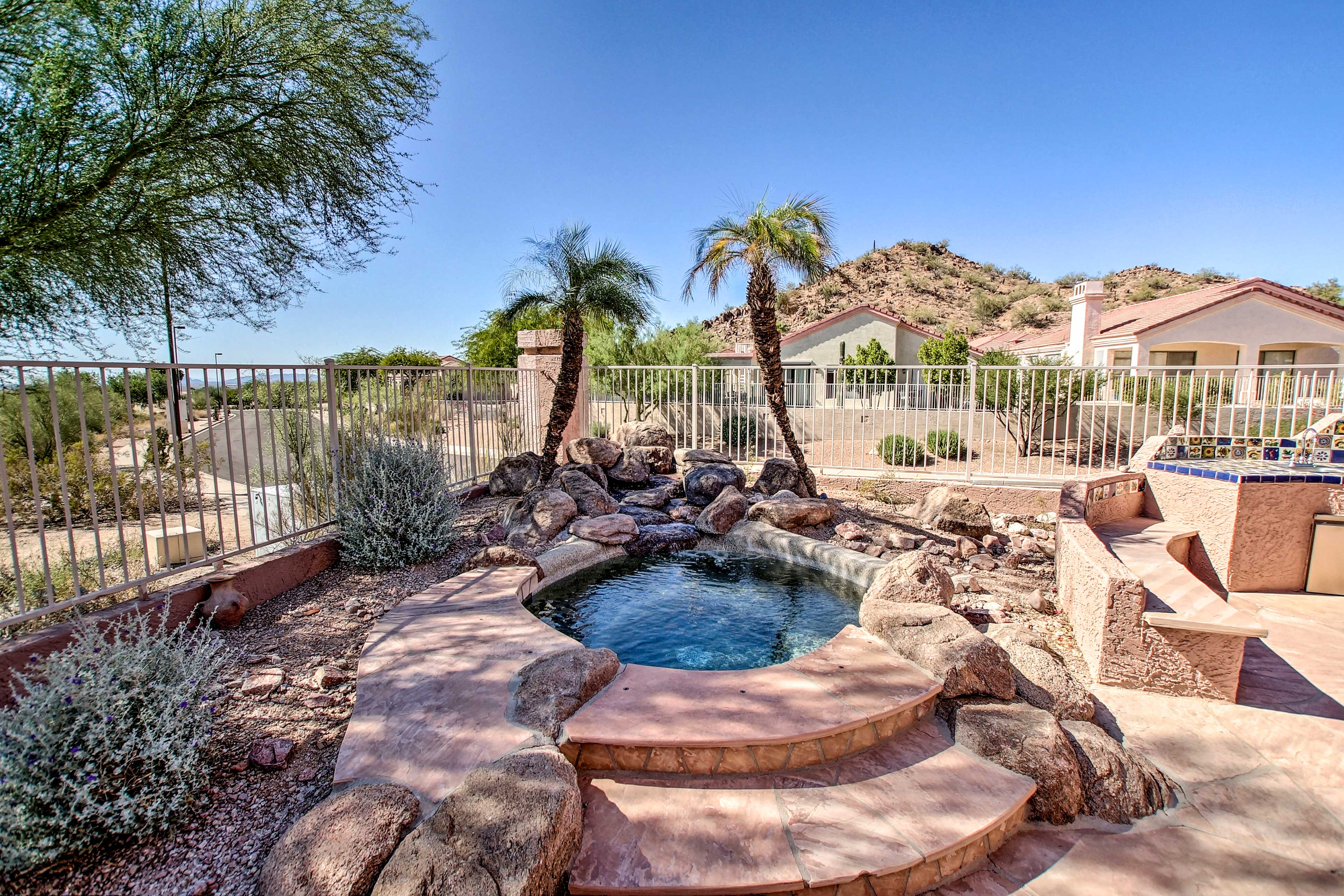 The in-ground hot tub offers a calming fountain feature.