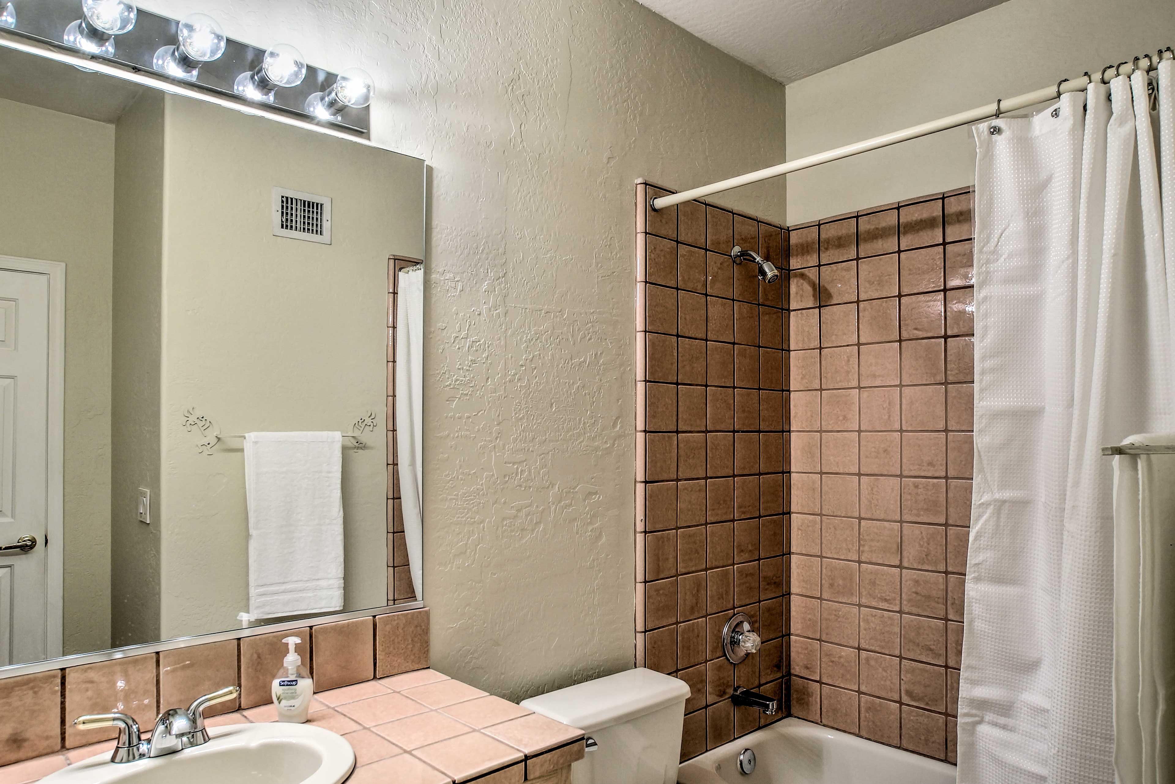 This bathroom features a shower/tub combination and ample lighting.