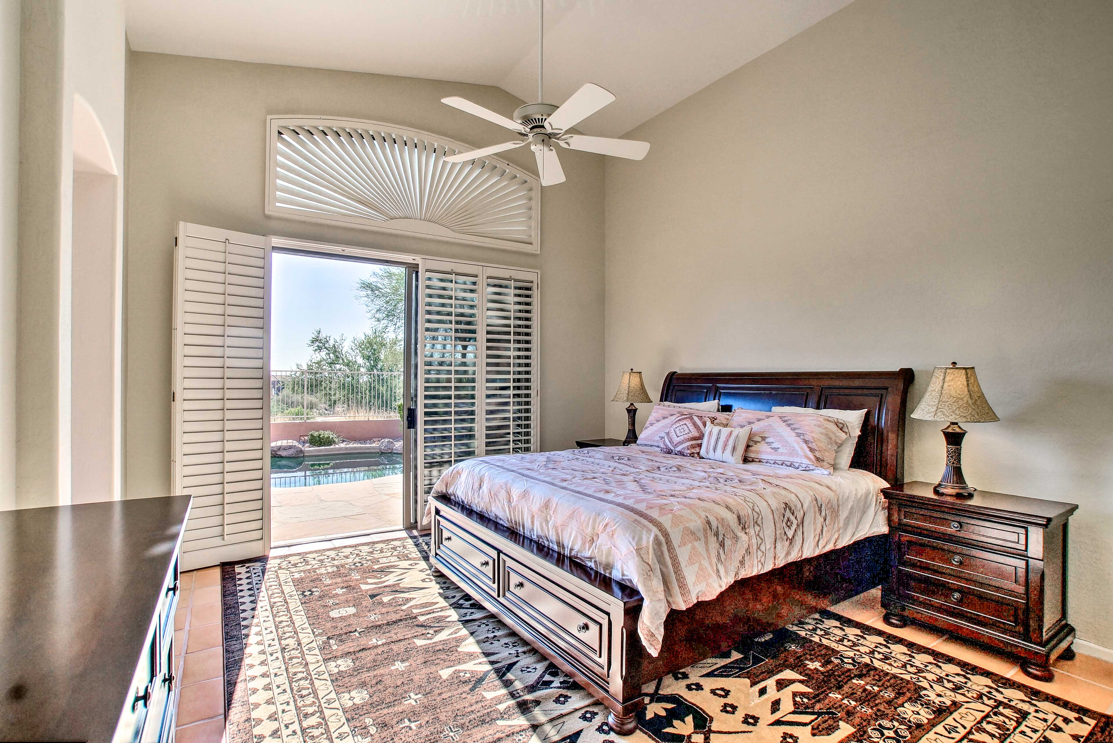 The luxurious master bedroom features a private entrance to the patio and pool.