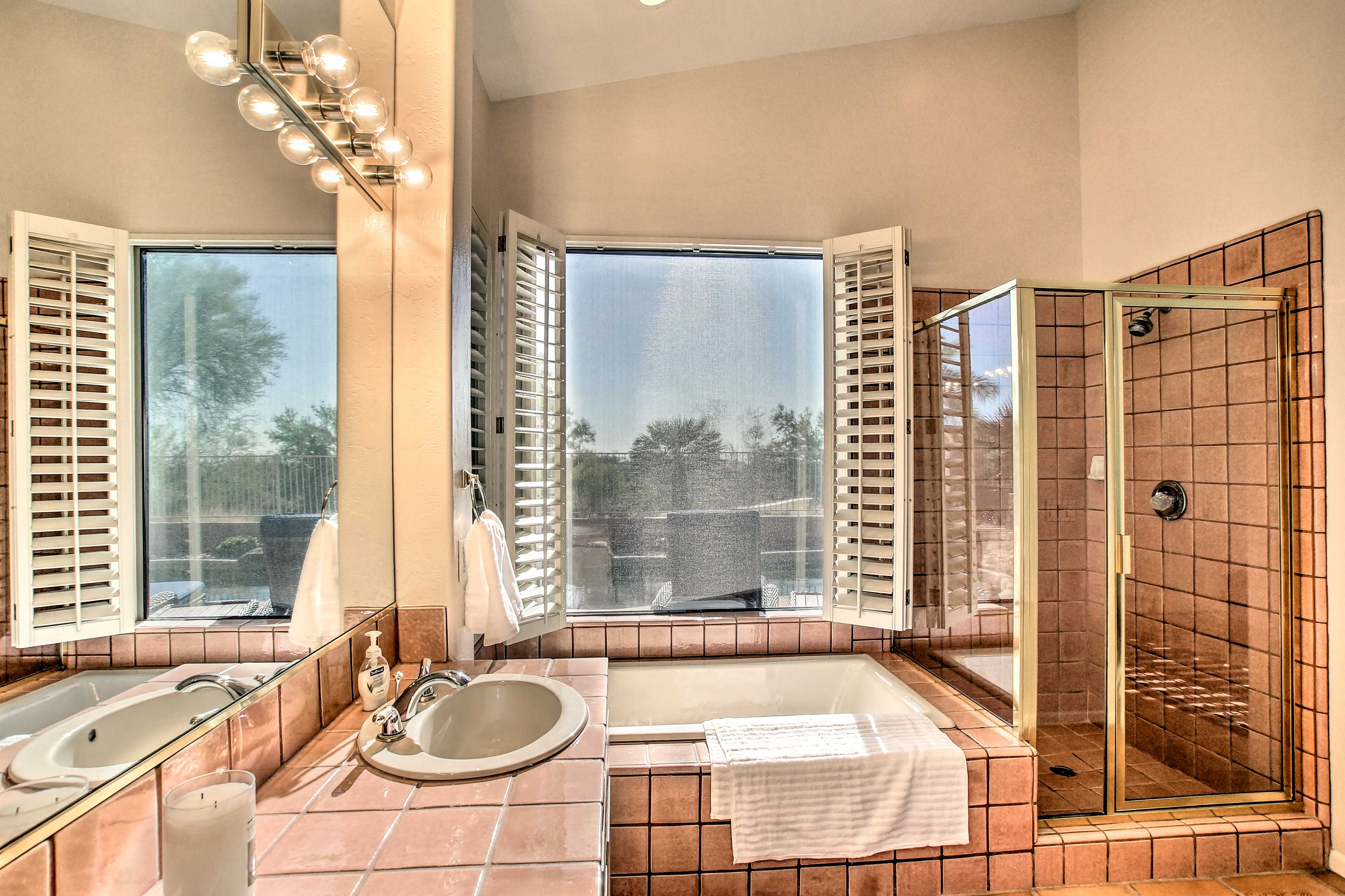 The master bathroom has a walk-in shower and bathtub with pool views.
