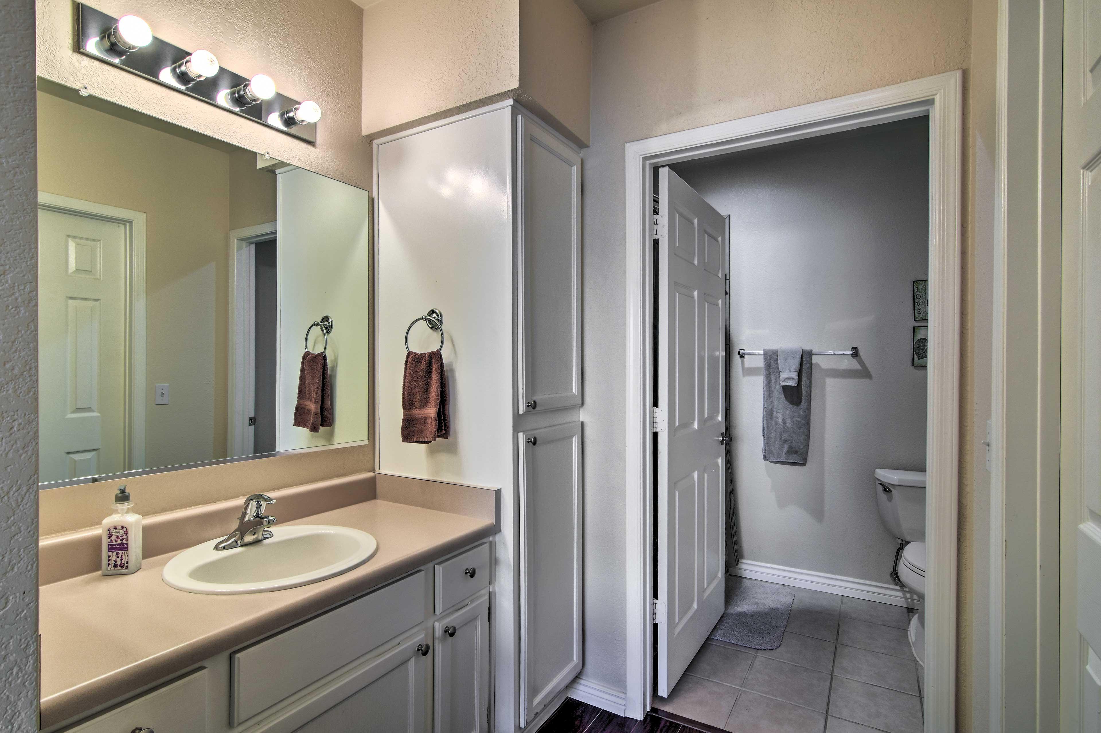 The en-suite bathroom has ample storage space.
