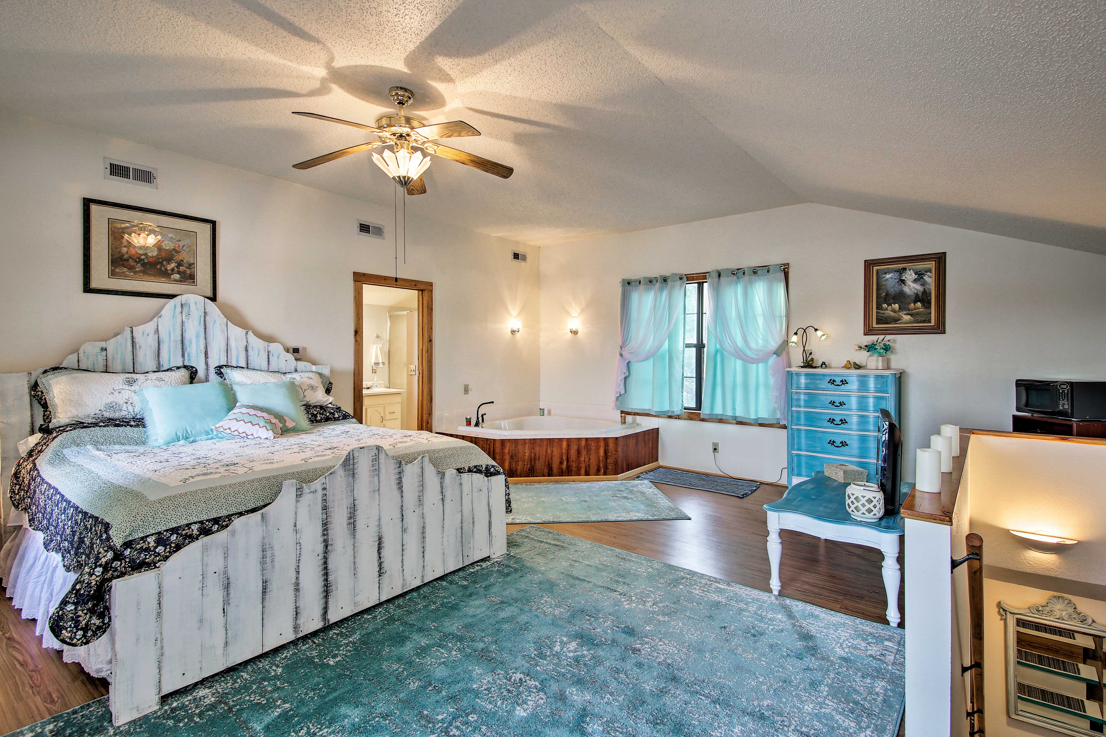 The master bedroom boasts a king-sized bed and bath tub.