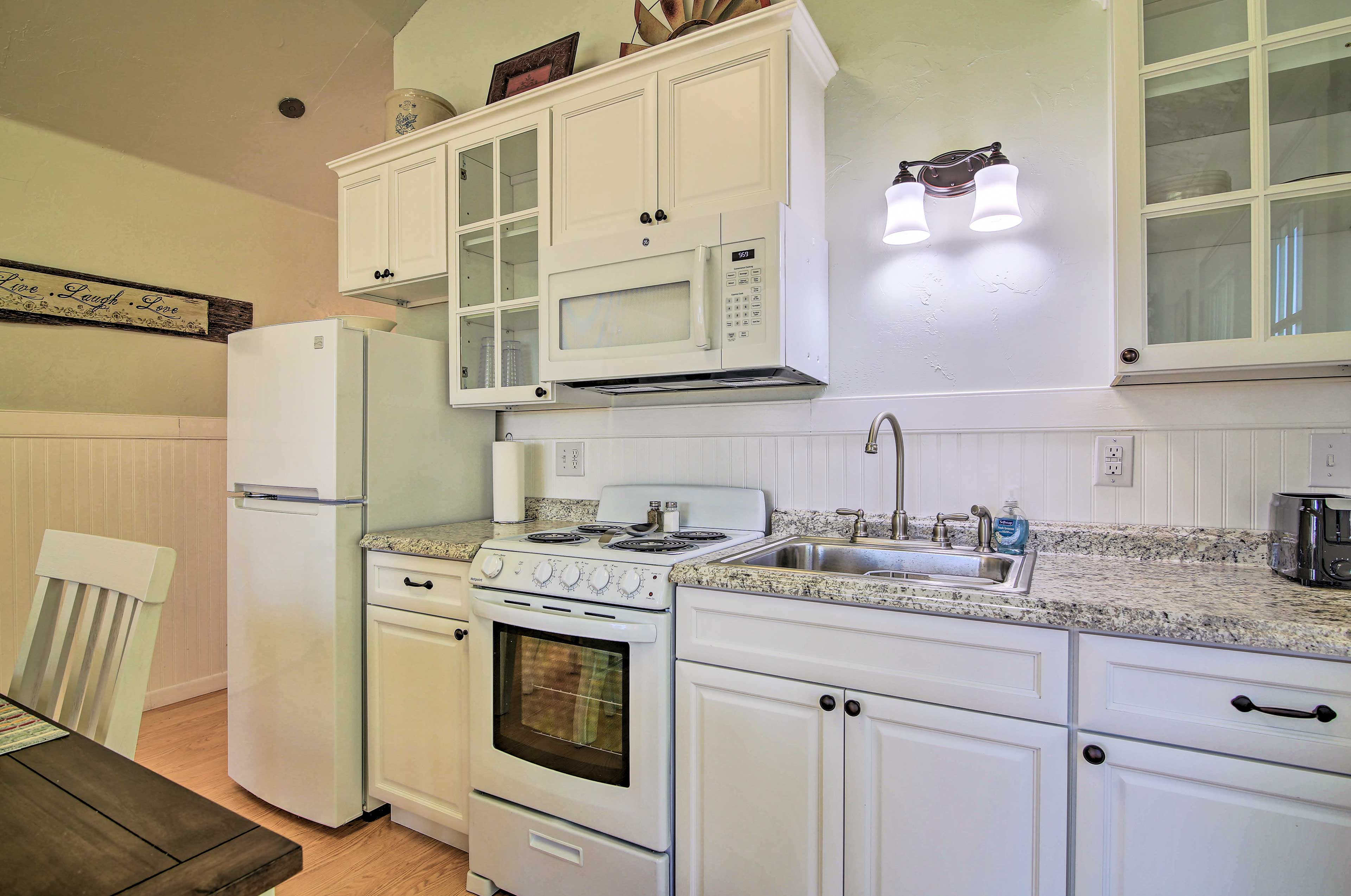 The kitchen offers granite countertops and white cabinetry.