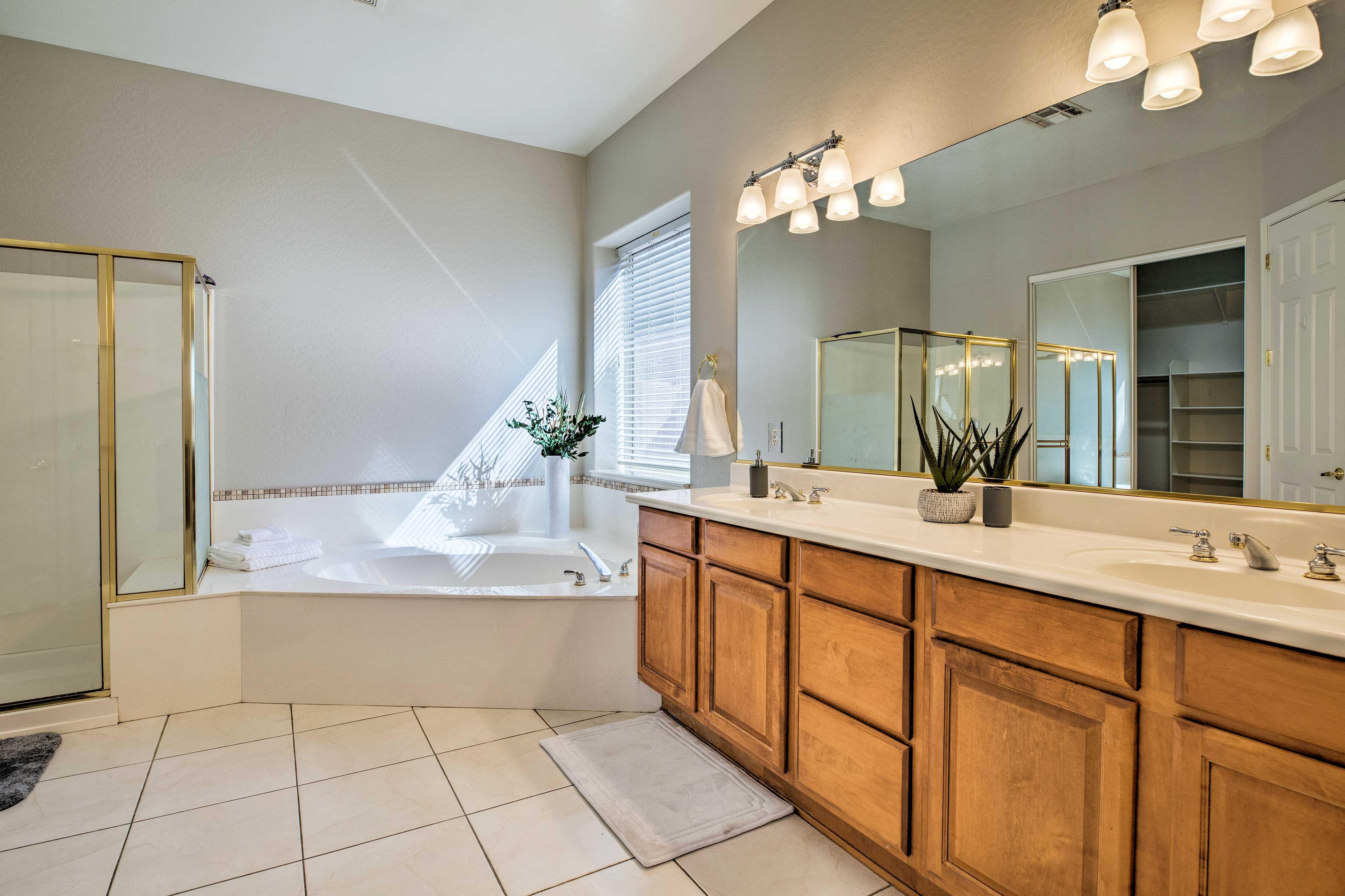 Double sinks, a deep soaking tub, & a walk-in shower make up the en-suite bath.