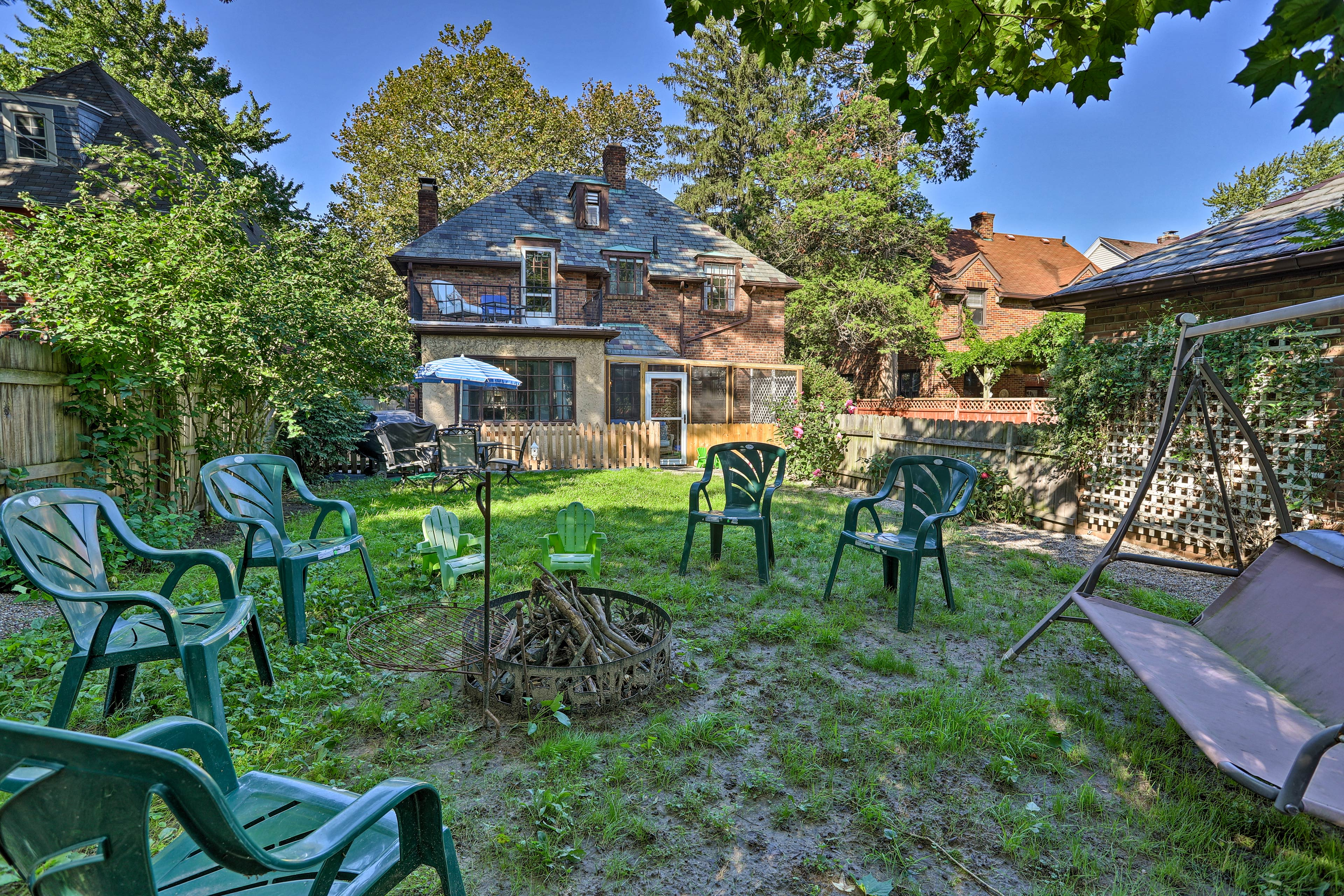 The vacation rental property includes a large yard, fire pit, & sunroom.