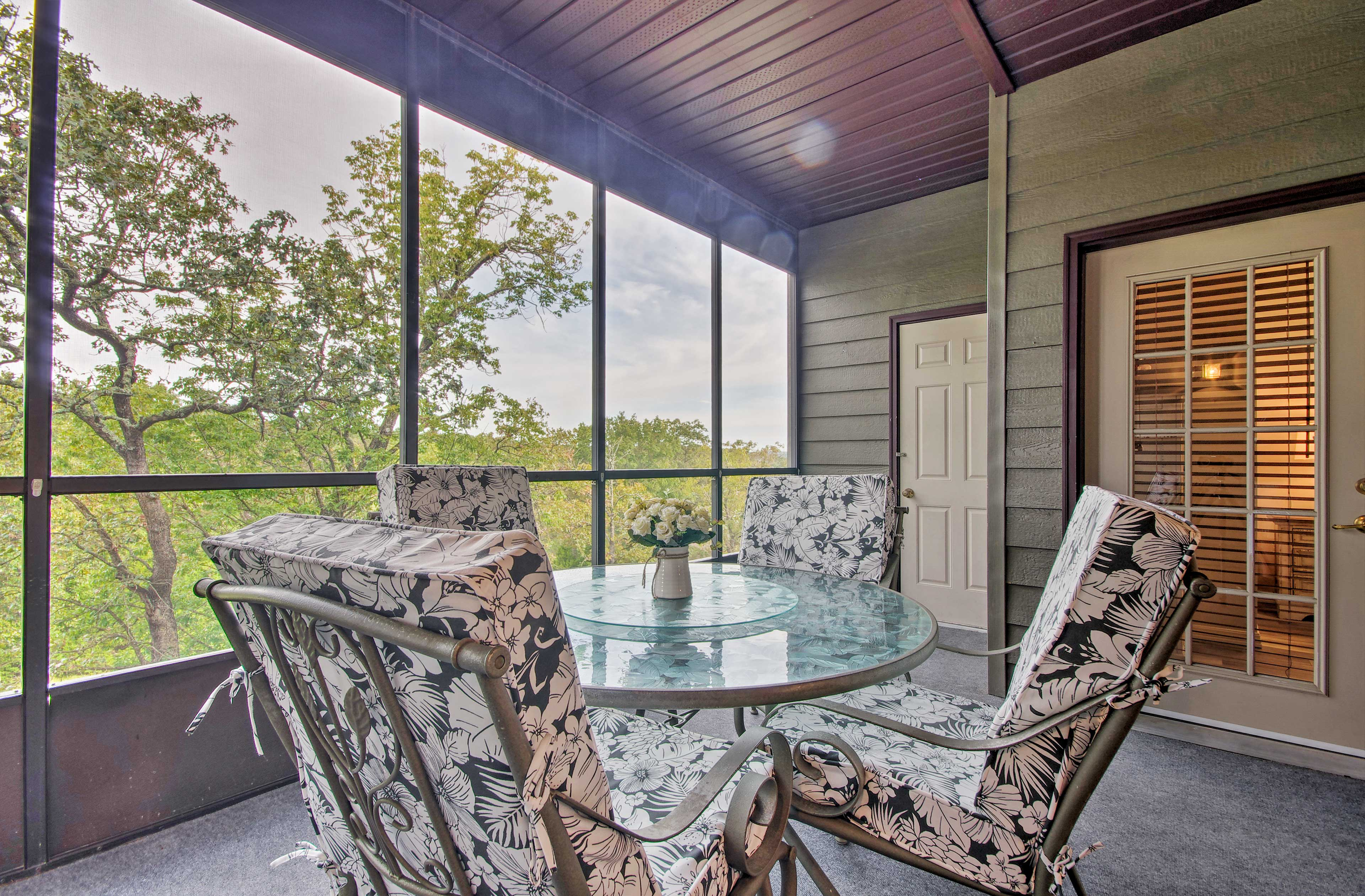 Dine outdoors on the screened-in balcony.
