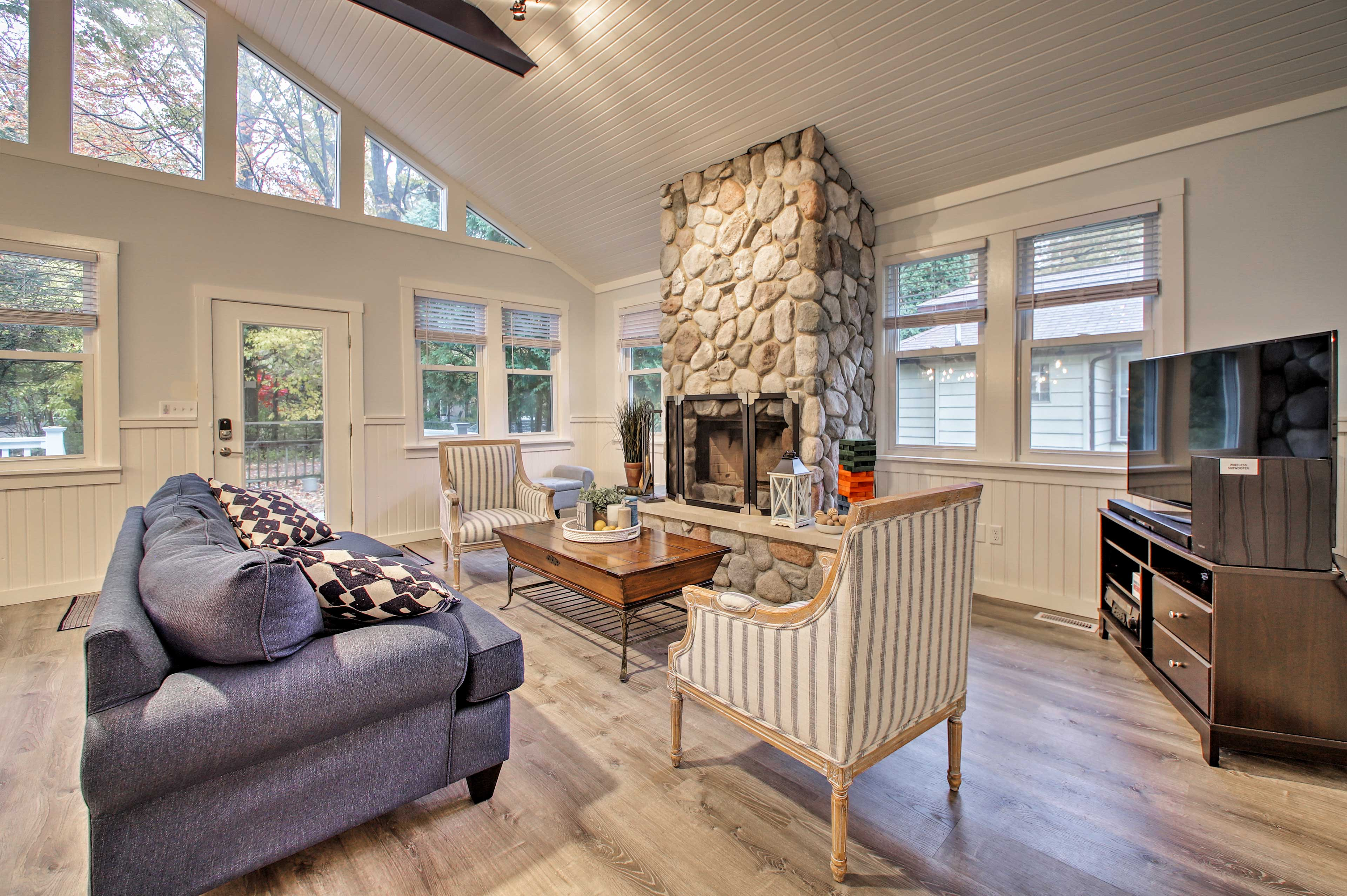 A large stone fireplace and vaulted ceilings highlight the living area.