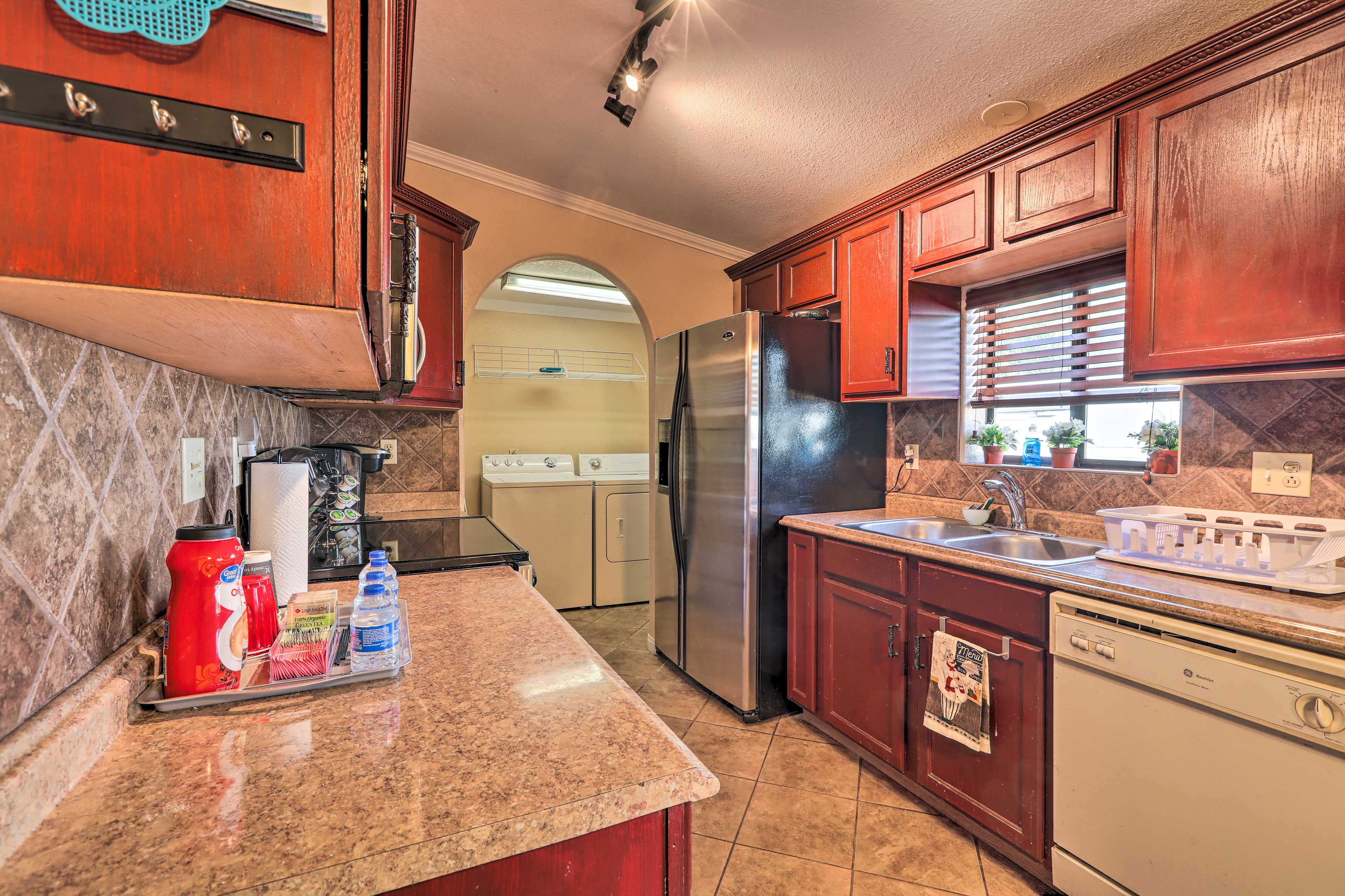 The laundry room is located at the end of the kitchen.