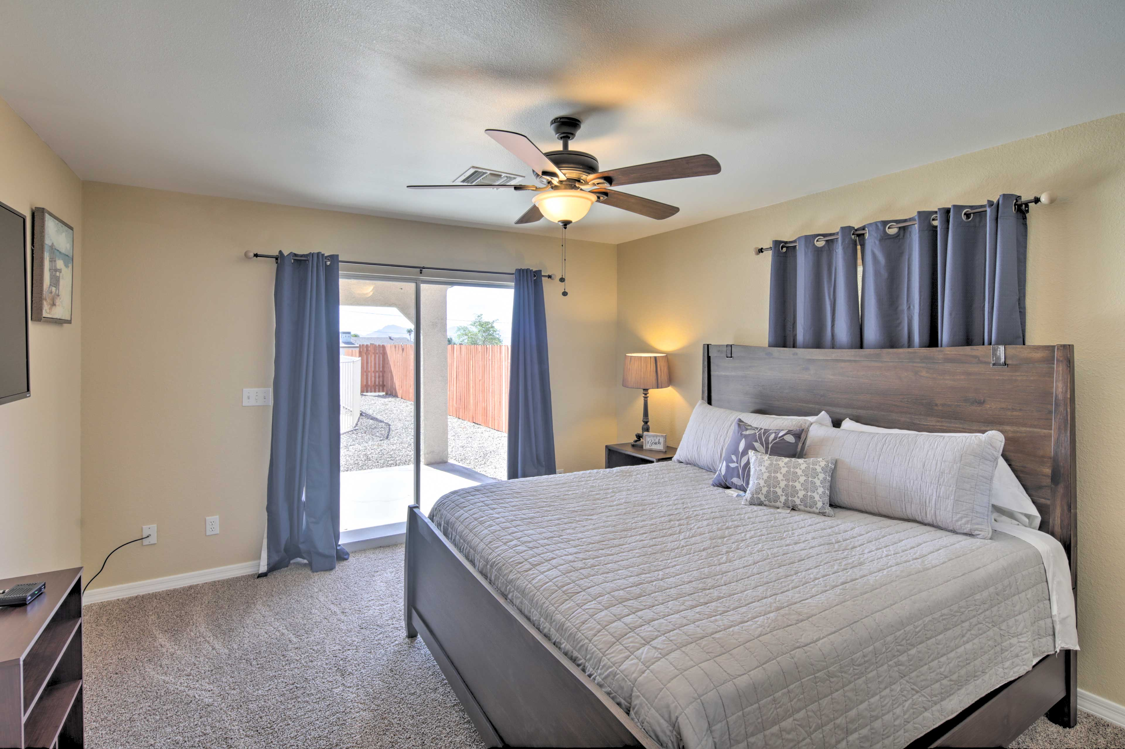 The master bedroom boasts a California king bed and patio access!
