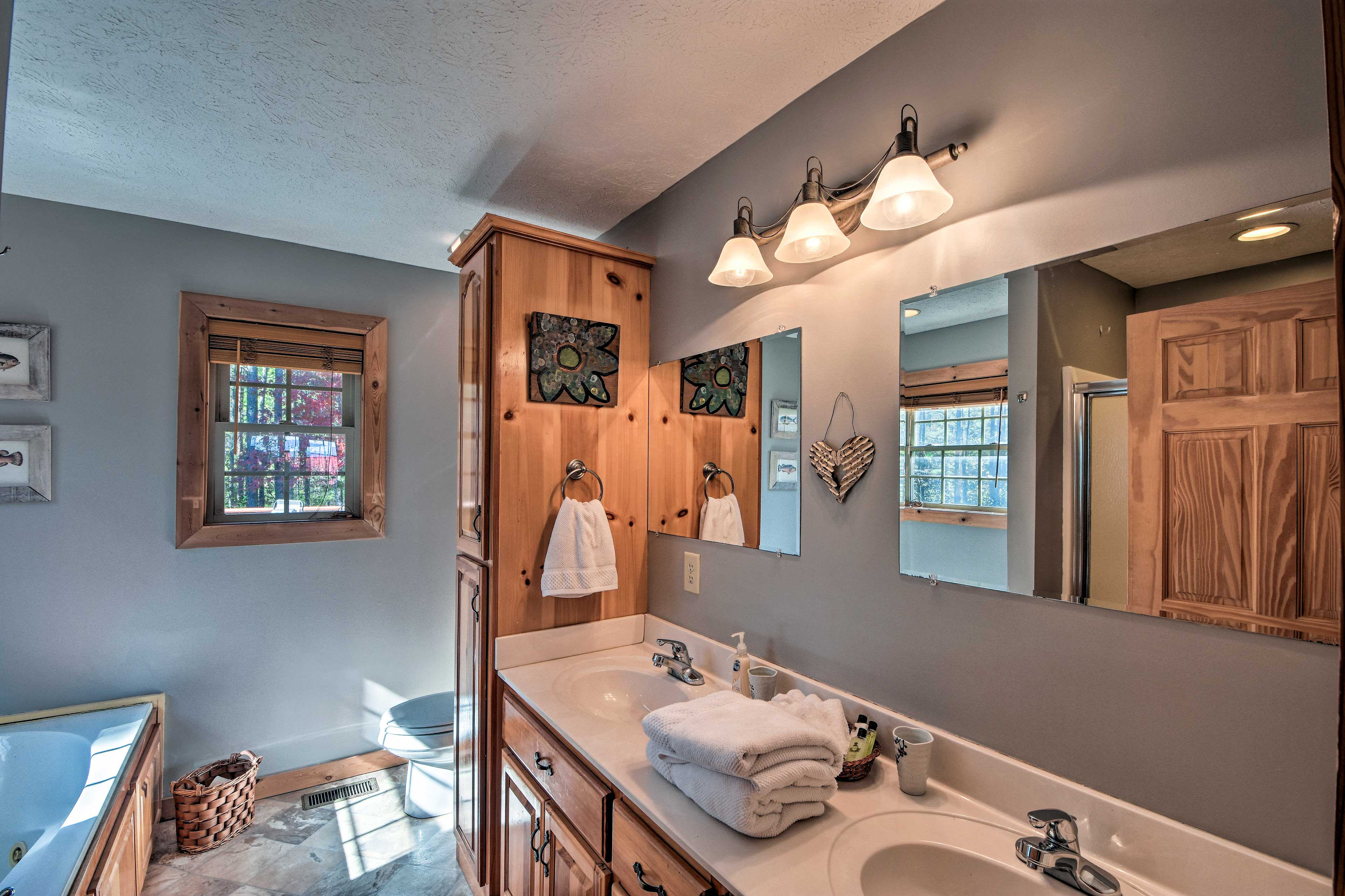 The master bathroom features a double vanity, a bathtub and walk-in shower.