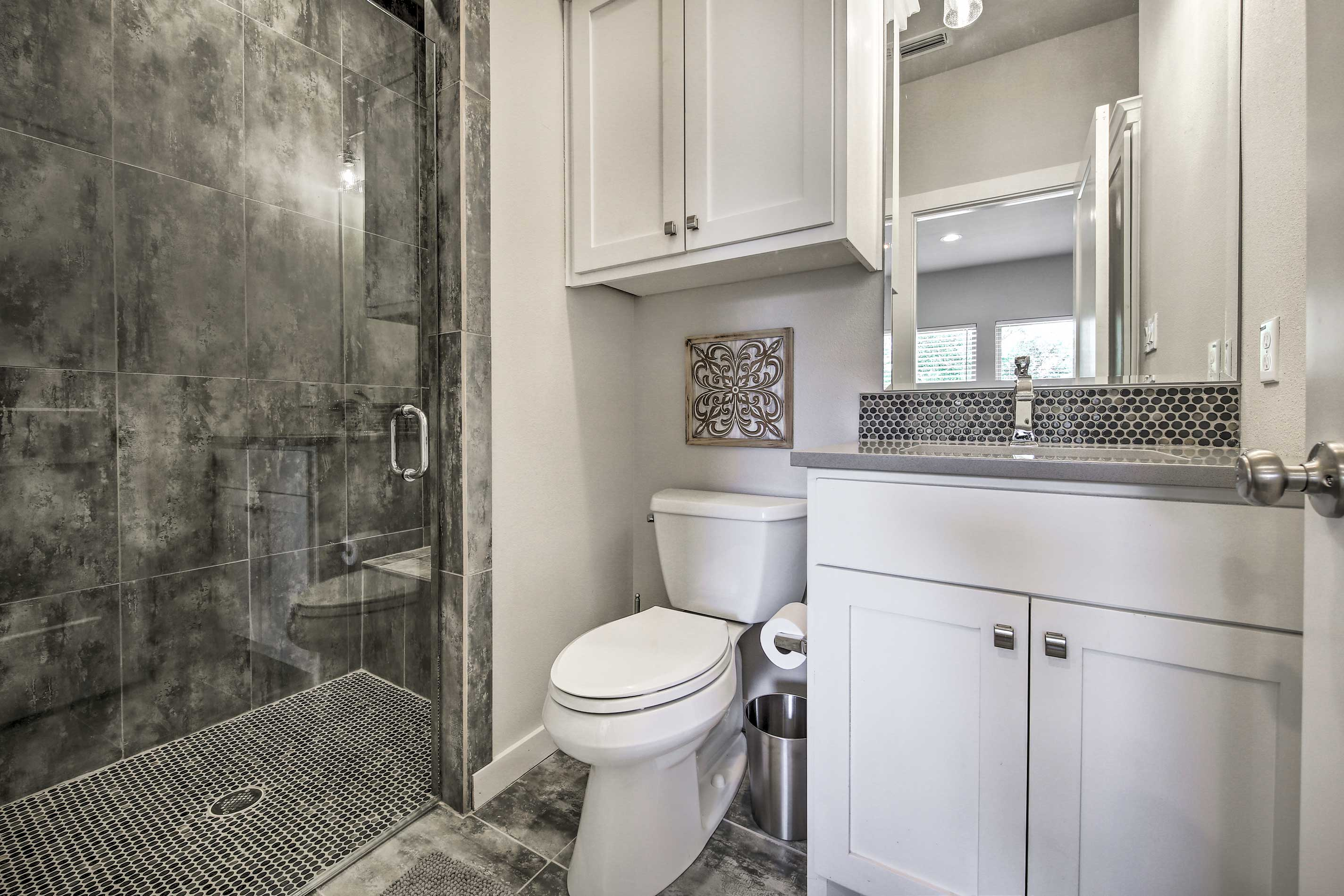The full bath contains a walk-in shower and mirrored vanity.