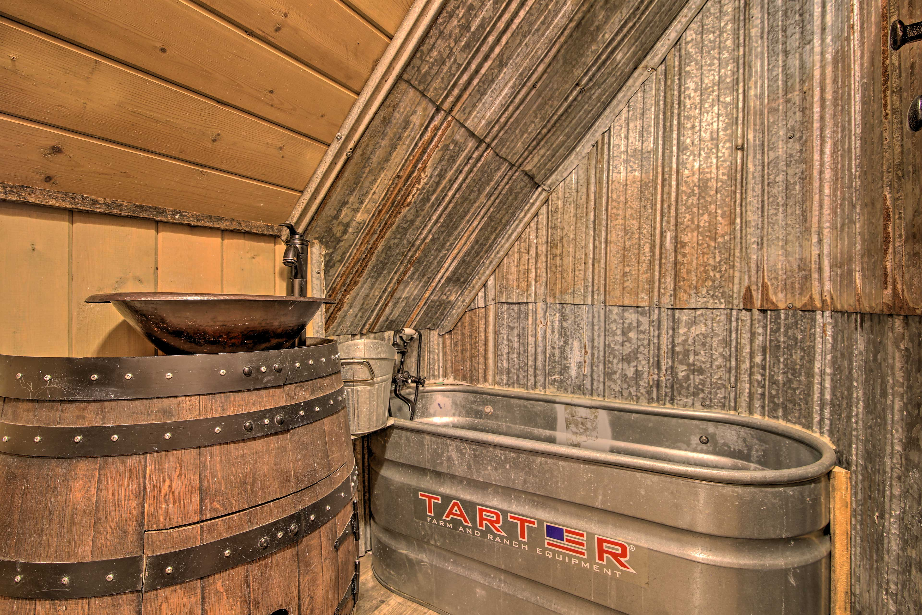 The second bathroom features an authentic, stainless steel farmhouse bathtub.