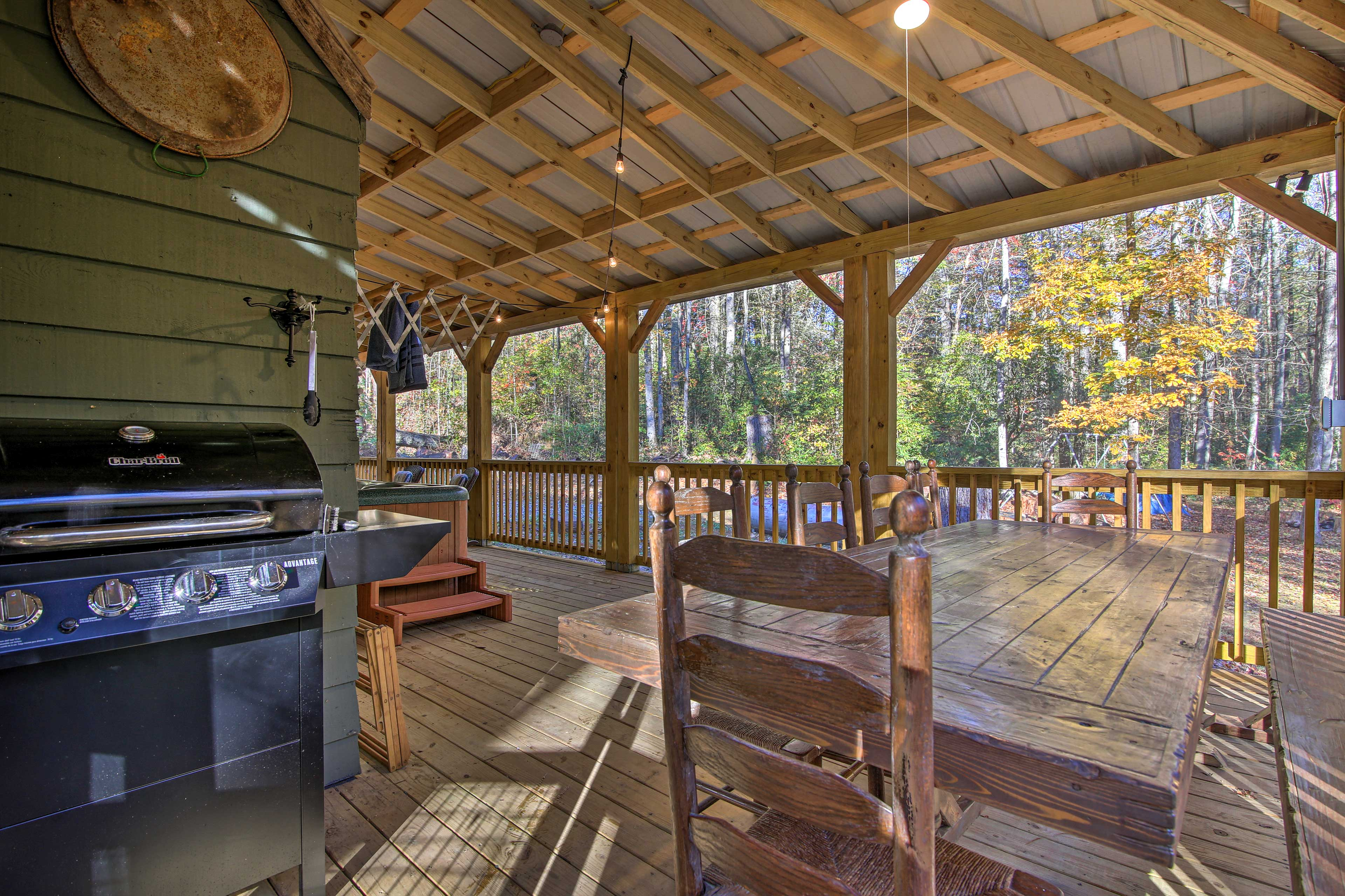 The screened-in portion of the porch has a gas grill, dining, and a hot tub.