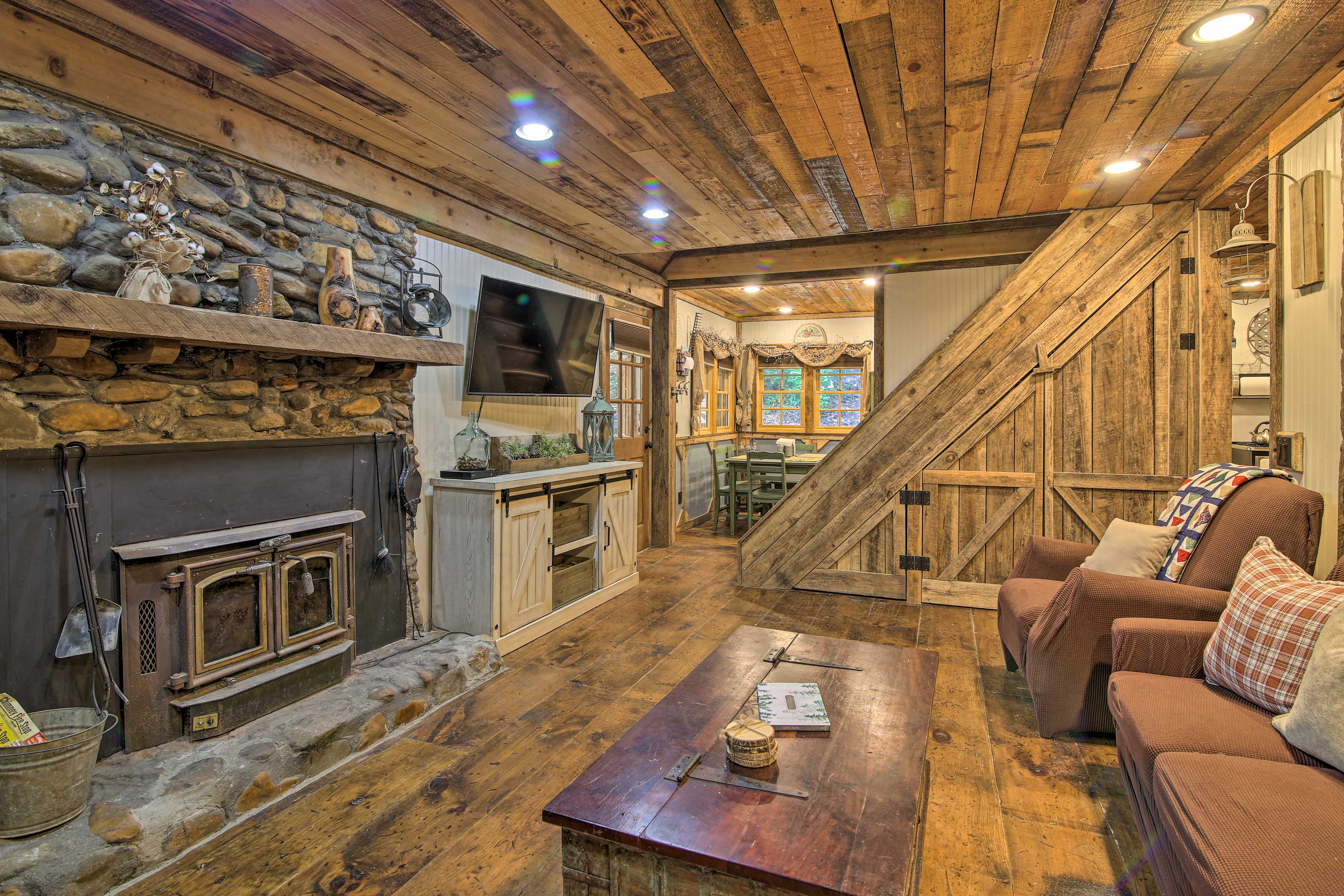 The living room has a fireplace with rubble masonry and eclectic, rustic decor.