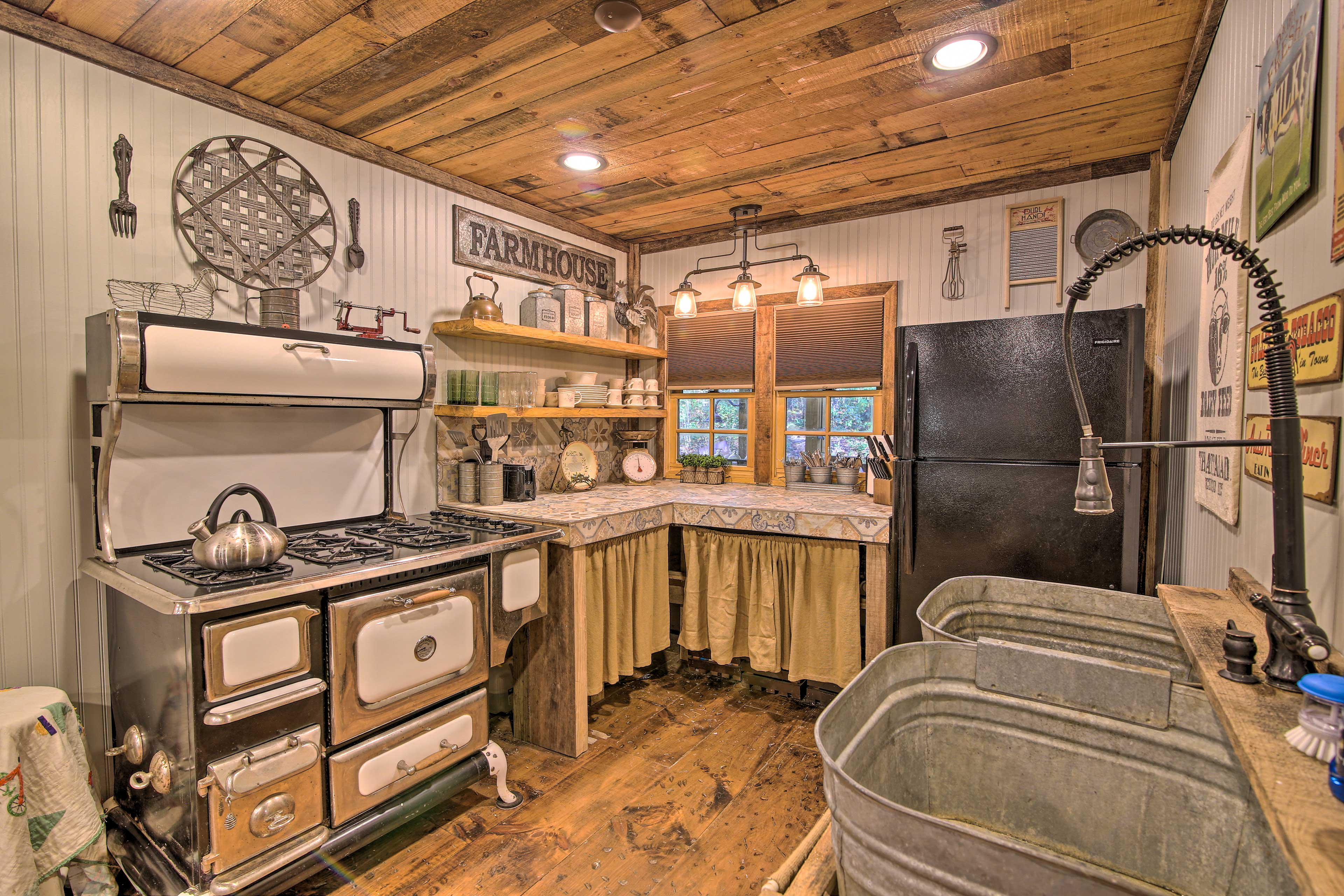The kitchen has kitschy touches, colorful countertops, and stainless barn sinks.