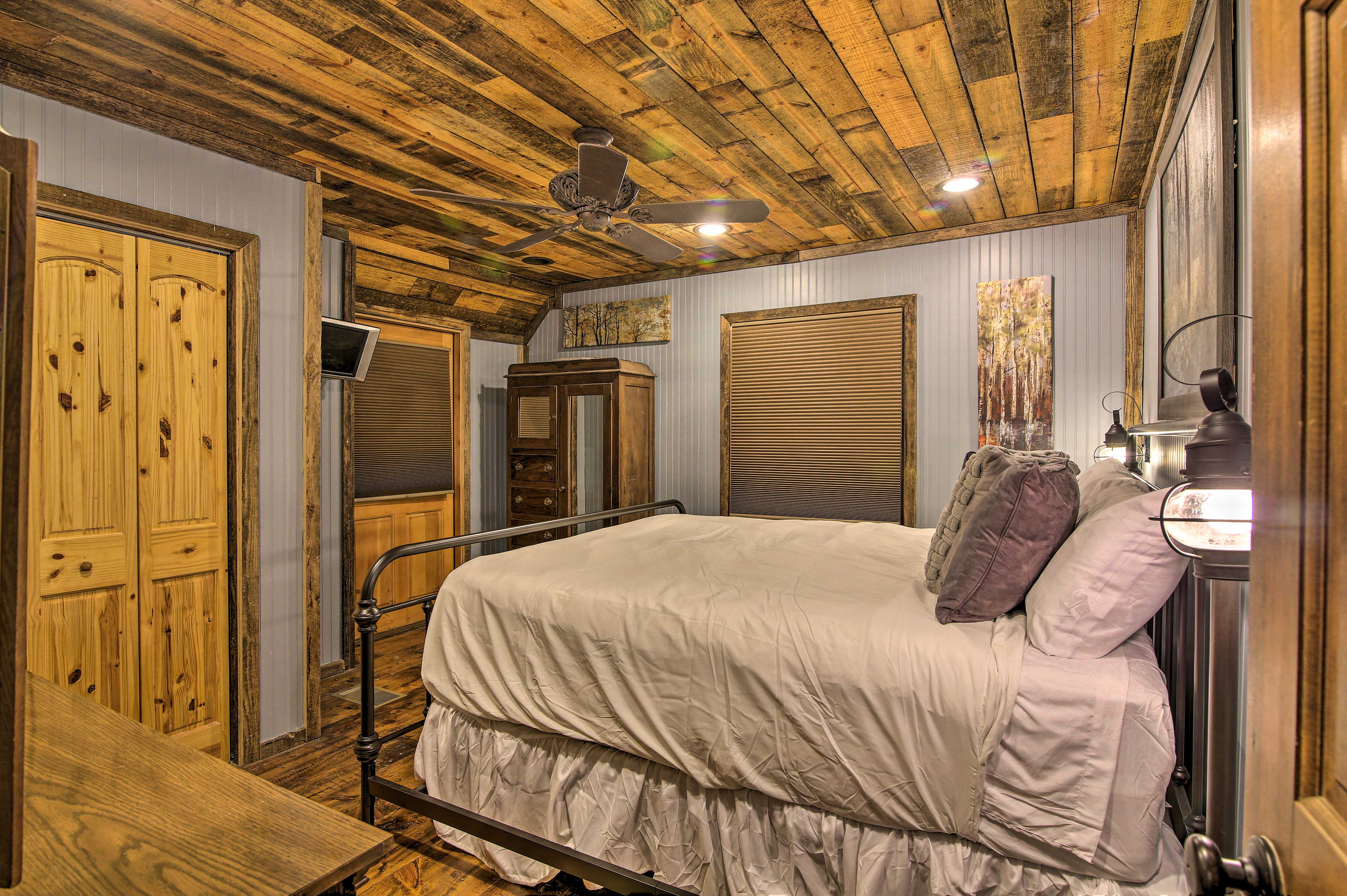 The master bedroom features a king bed, flat-screen TV, and wooden detailing.
