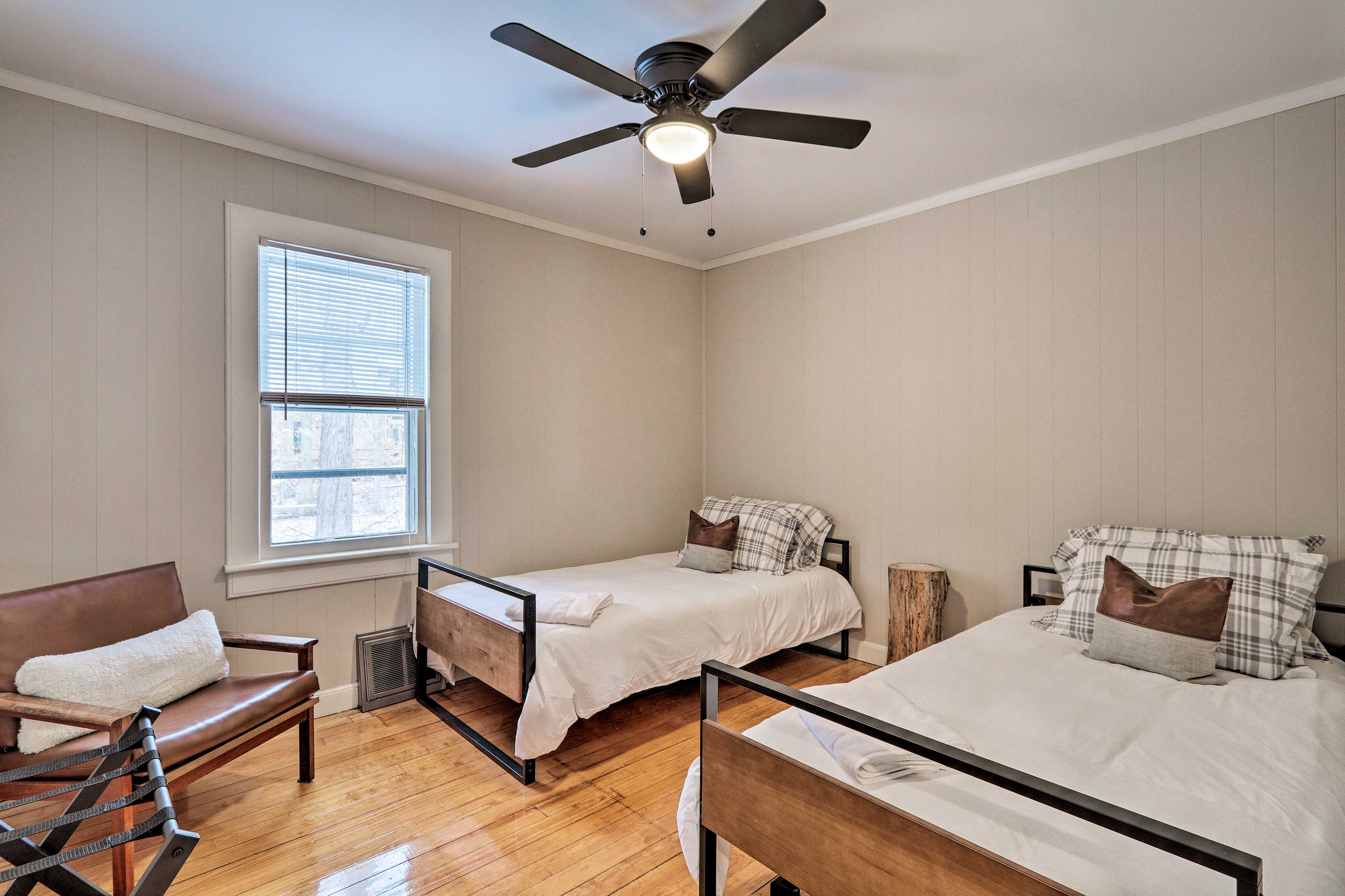 The second children's bedroom features a leather chair as well as 2 twin beds.