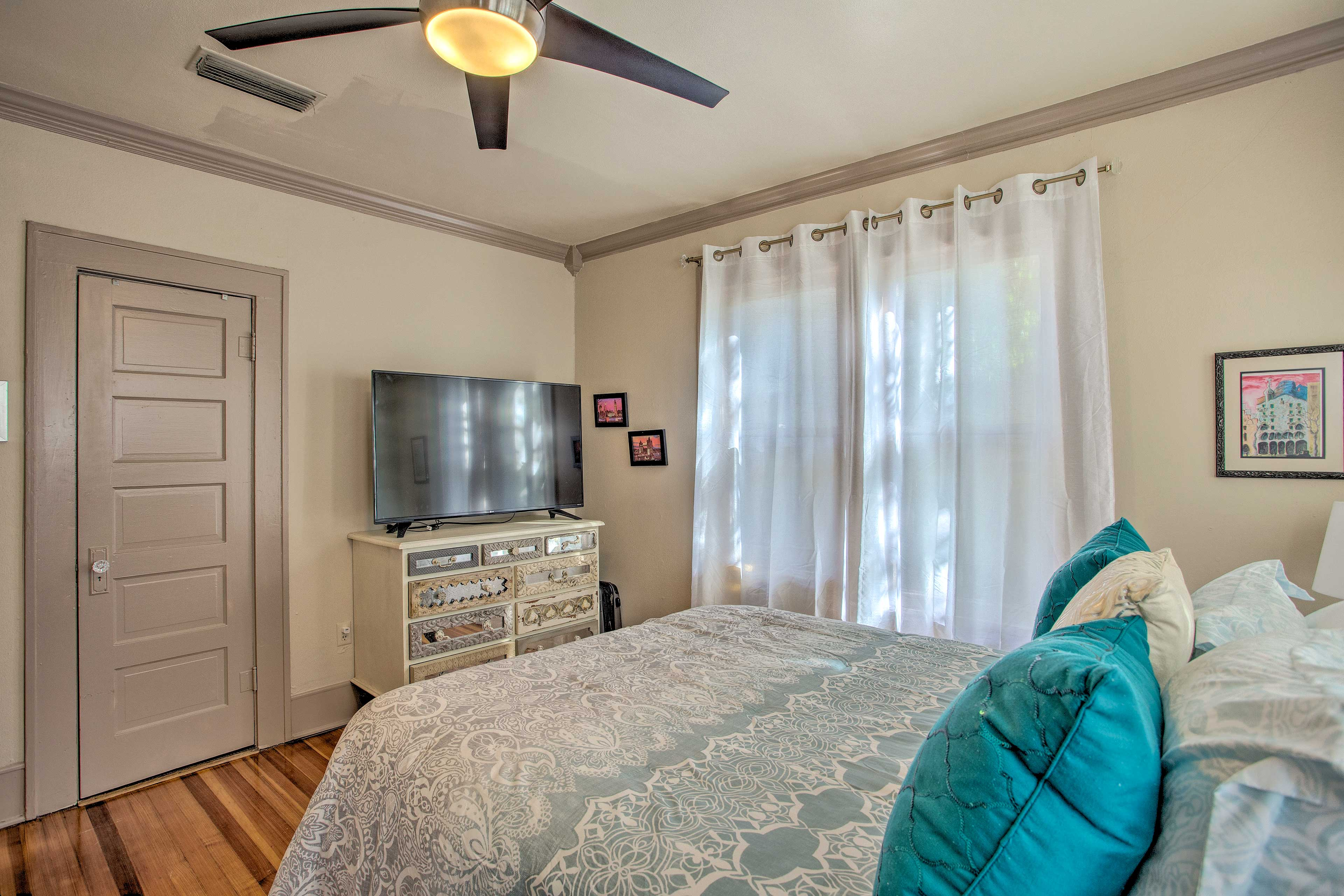 The bedroom features a queen bed and flat-screen TV.