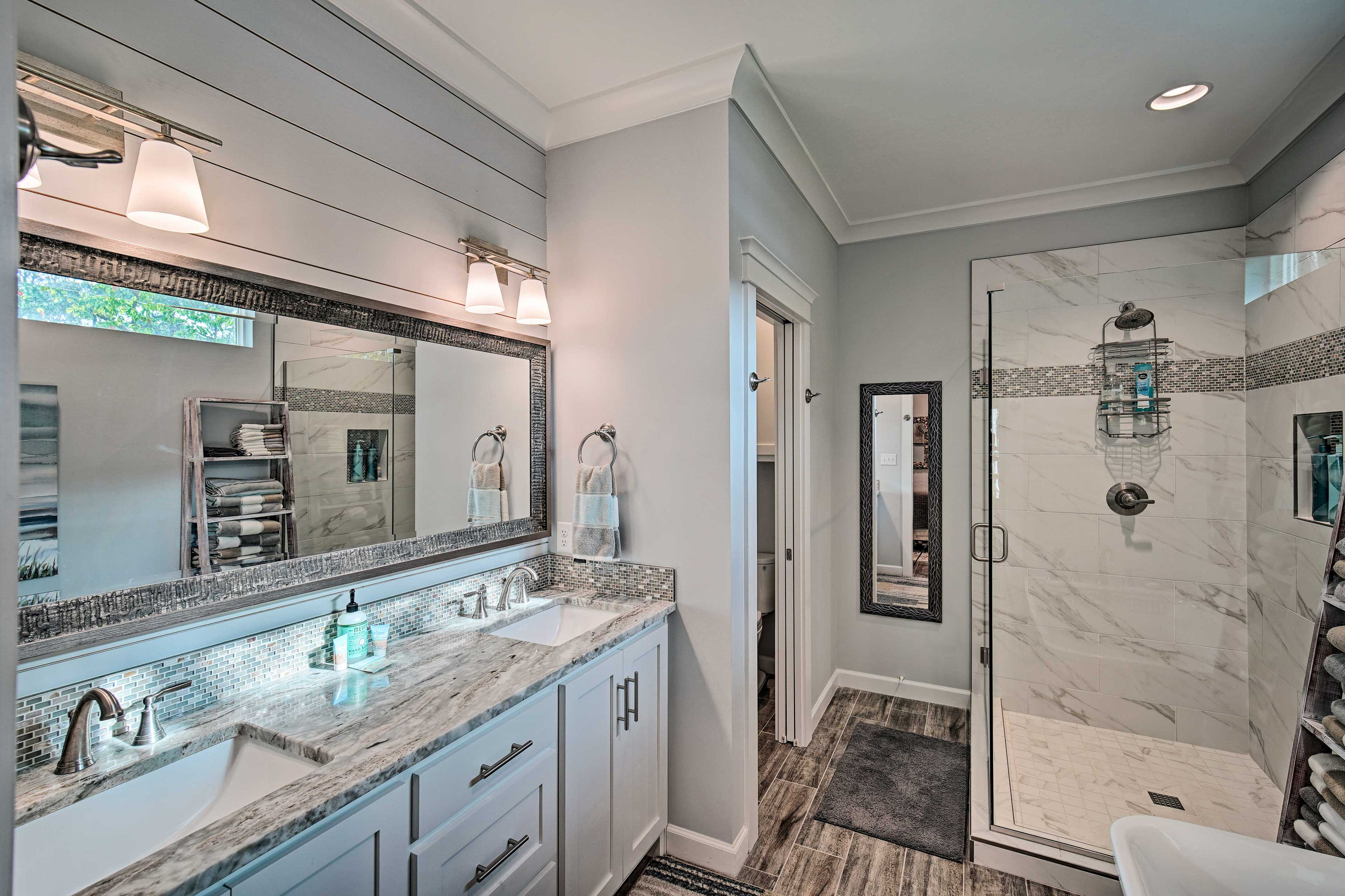 This sleek bathroom offers a dual-sink vanity and a marble-tiled shower.