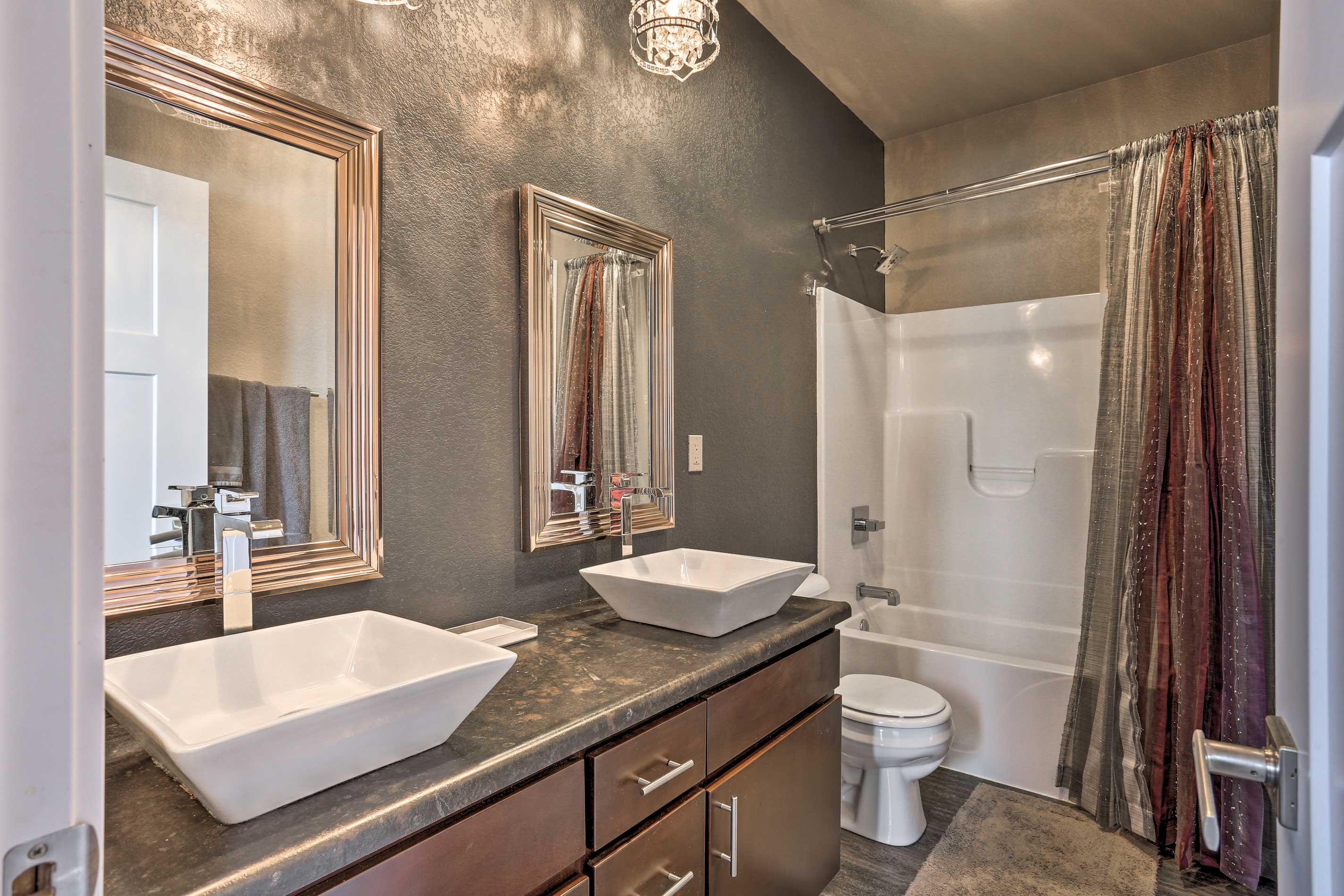This second bathroom features dual sinks and a shower/tub combo.