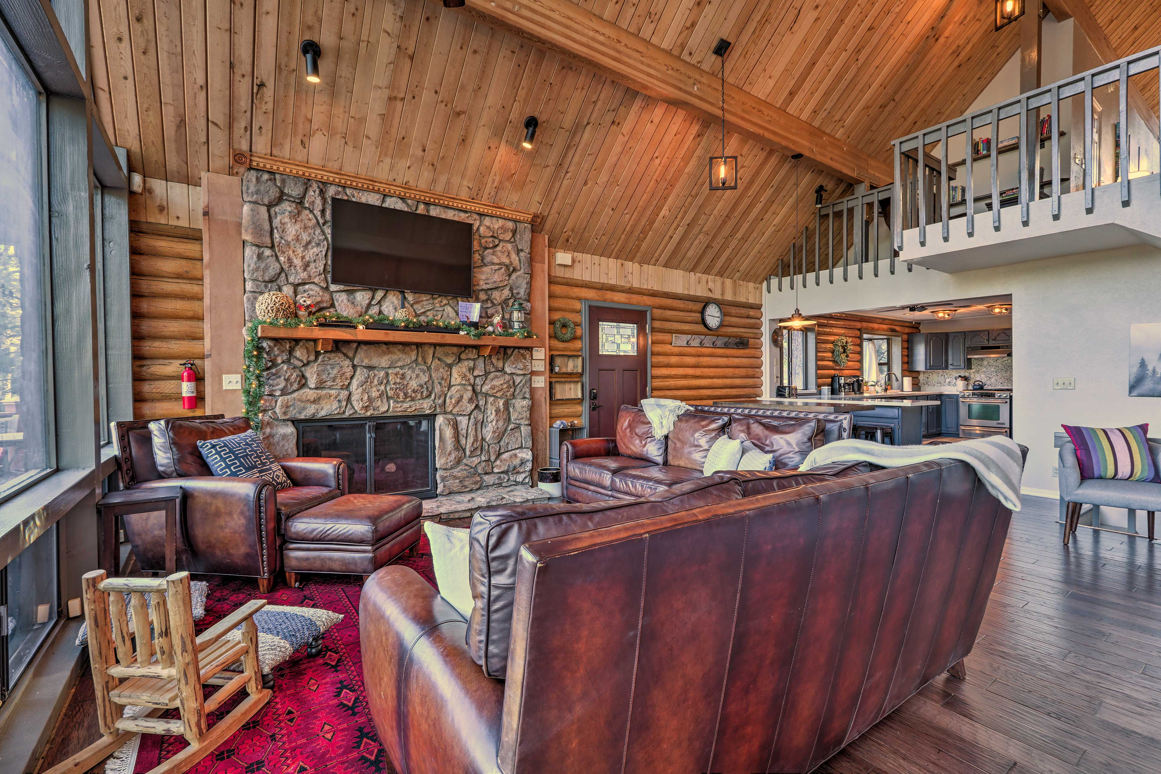 The massive living room boasts cathedral ceilings, knotty-pine accents, and more