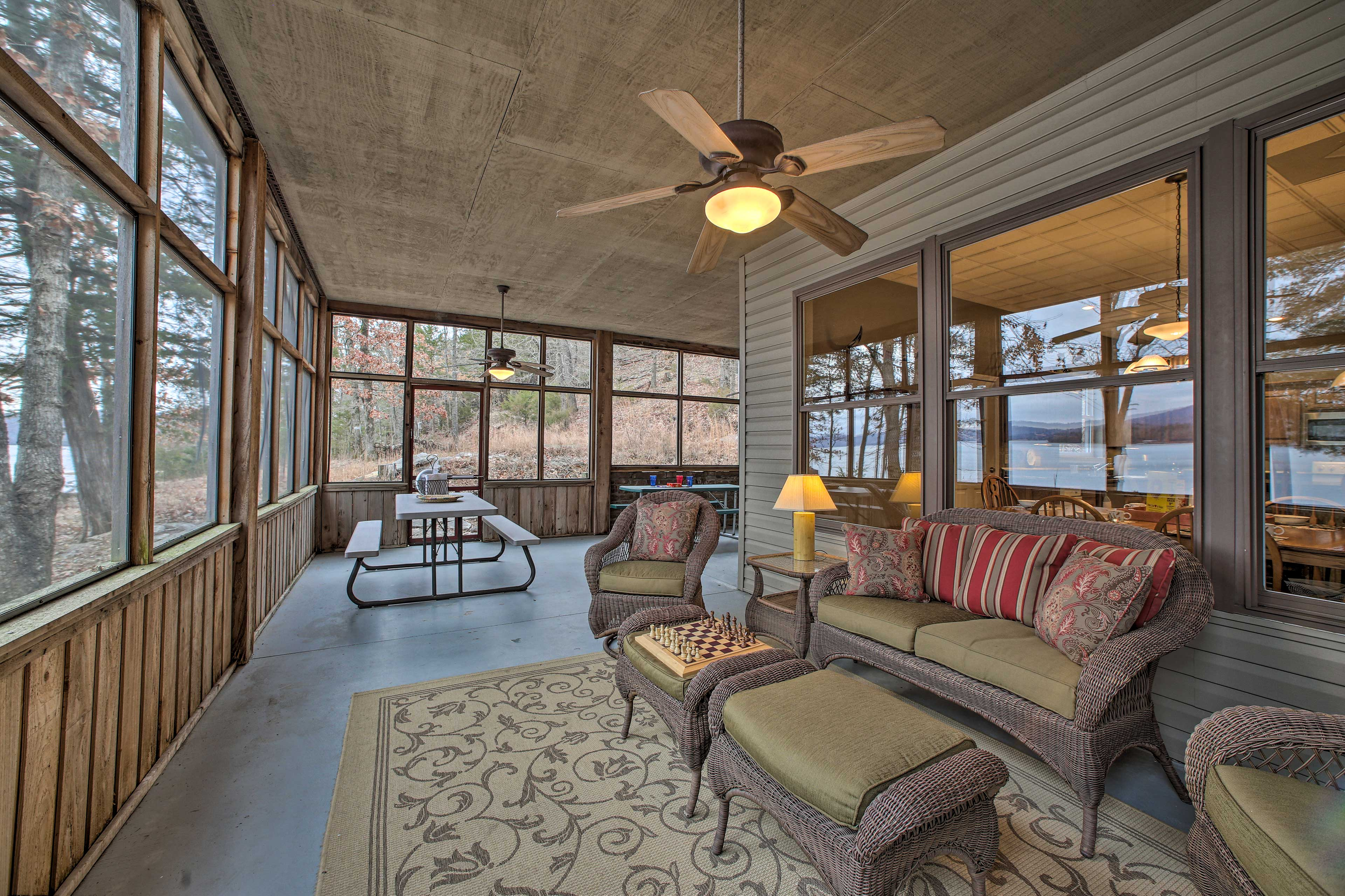 The screened-in porch features plenty of seating, 2 picnic tables, and a grill!